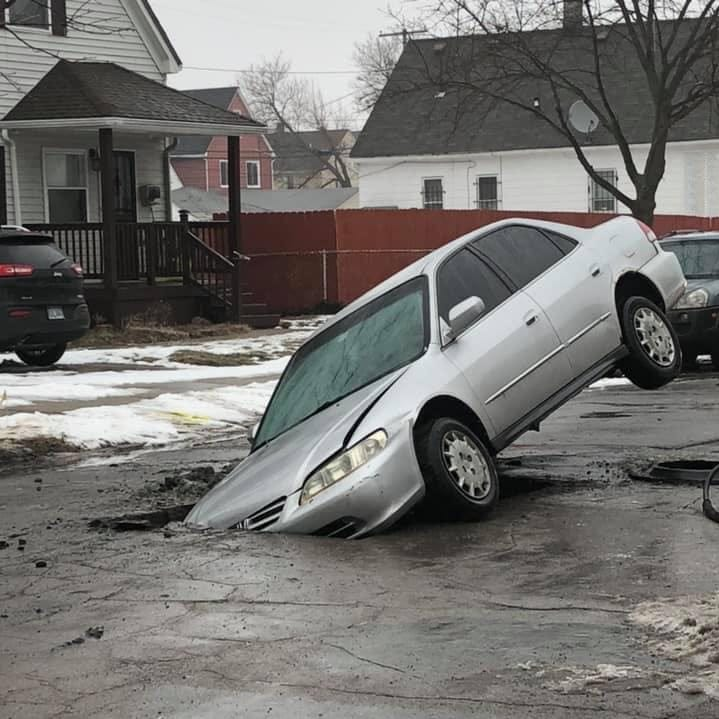 Photos of car stuck in huge Hamtramck hole spread across social media