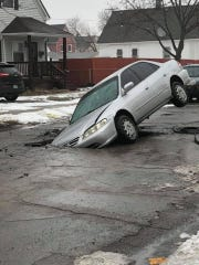 A car that had gotten stuck in a hole on Goodson Street in Hamtramck on Wednesday, Feb. 20, 2019.