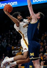 Jordan Murphy goes for a layup as Michigan's Jon Teske tries to block the shot in the first half Thursday in Minneapolis.