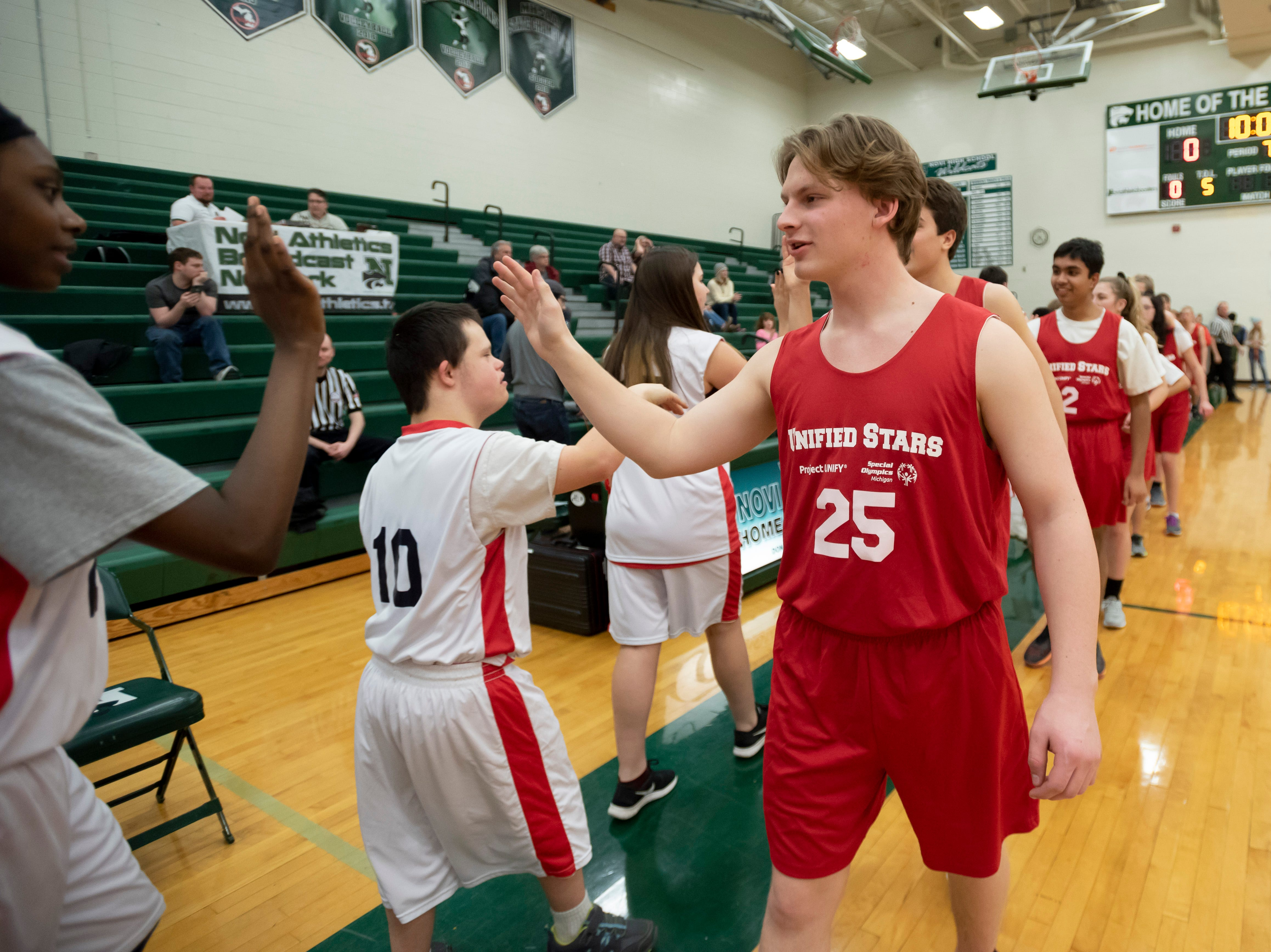 Plymouth-Canton's Eric Unruh high fives the players from Livonia Franklin after a game.