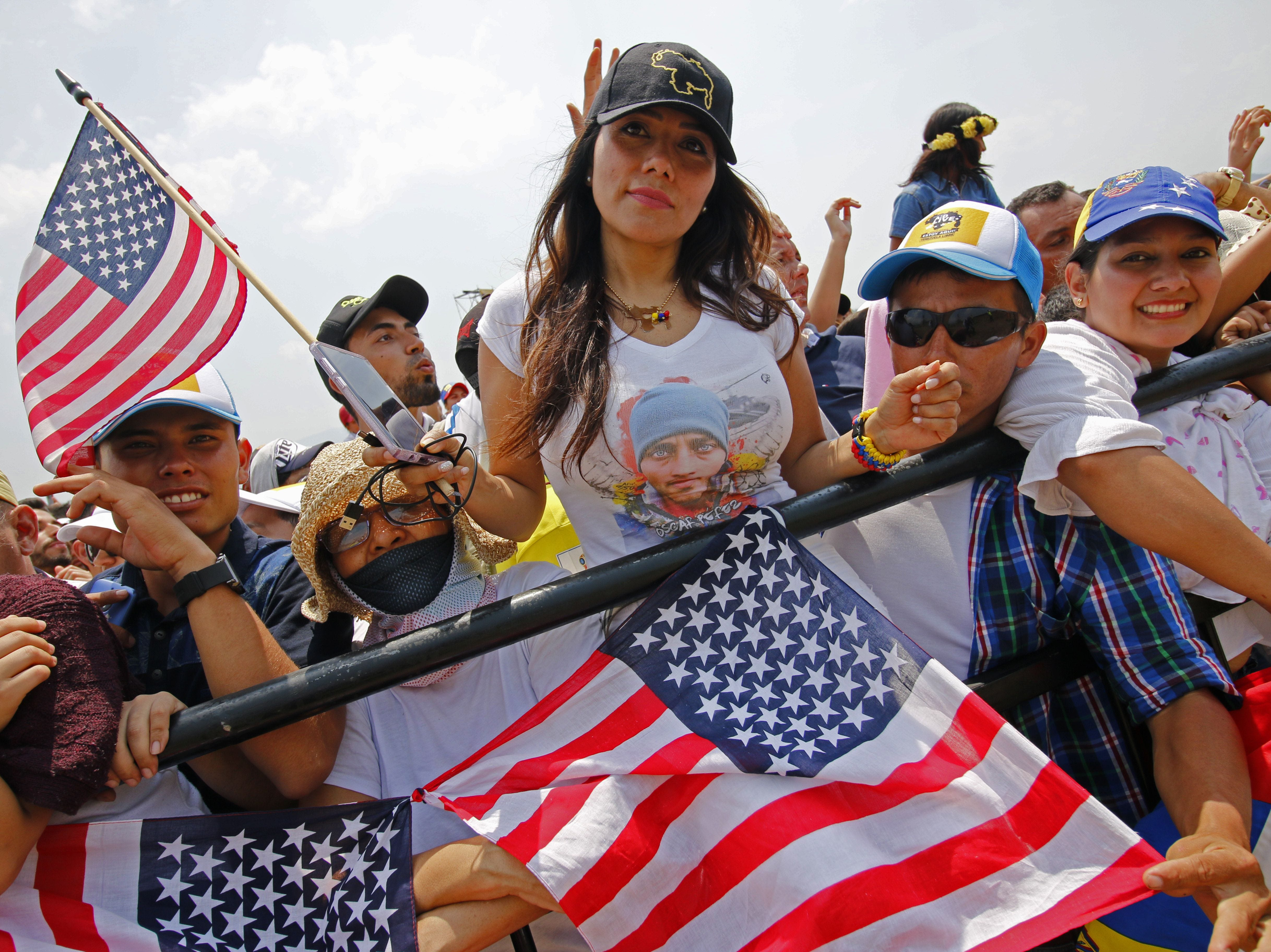 """A woman holds a U.S. flag while taking part in the """"Venezuela Aid Live"""" concert to assist the relief effort at Tienditas International Bridge in Cucuta, Colombia, on Feb. 22, 2019. The concert was organized by British billionaire Richard Branson. Venezuela's political tug-of-war morphed into a battle of the bands on Friday, with dueling government and opposition pop concerts ahead of a weekend showdown over the entry of badly needed food and medical aid."""