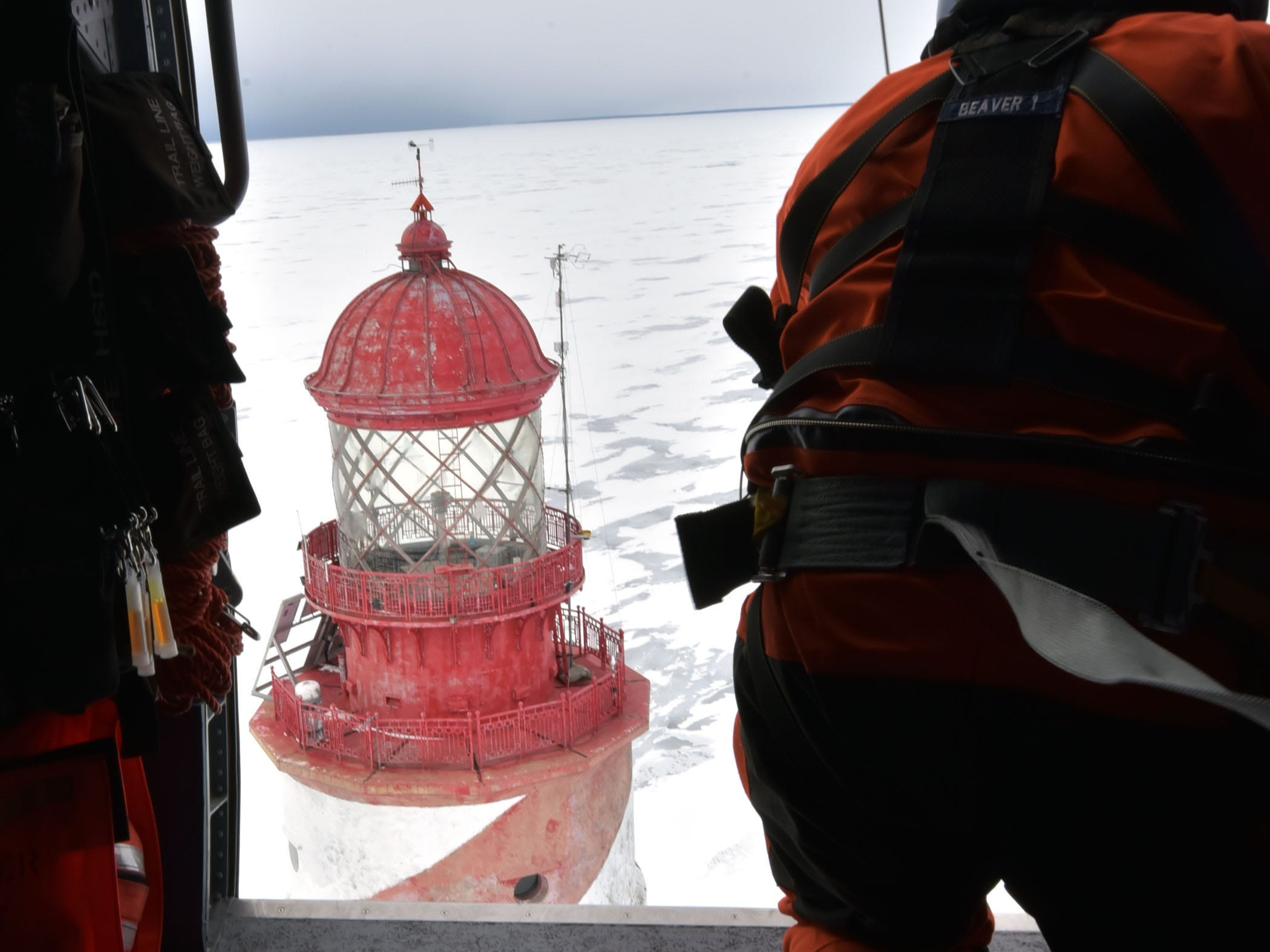 The U.S. Coast Guard's  John Axelson drops a basket 130 feet to the deck of the White Shoal Lighthouse in upper Lake Michigan.