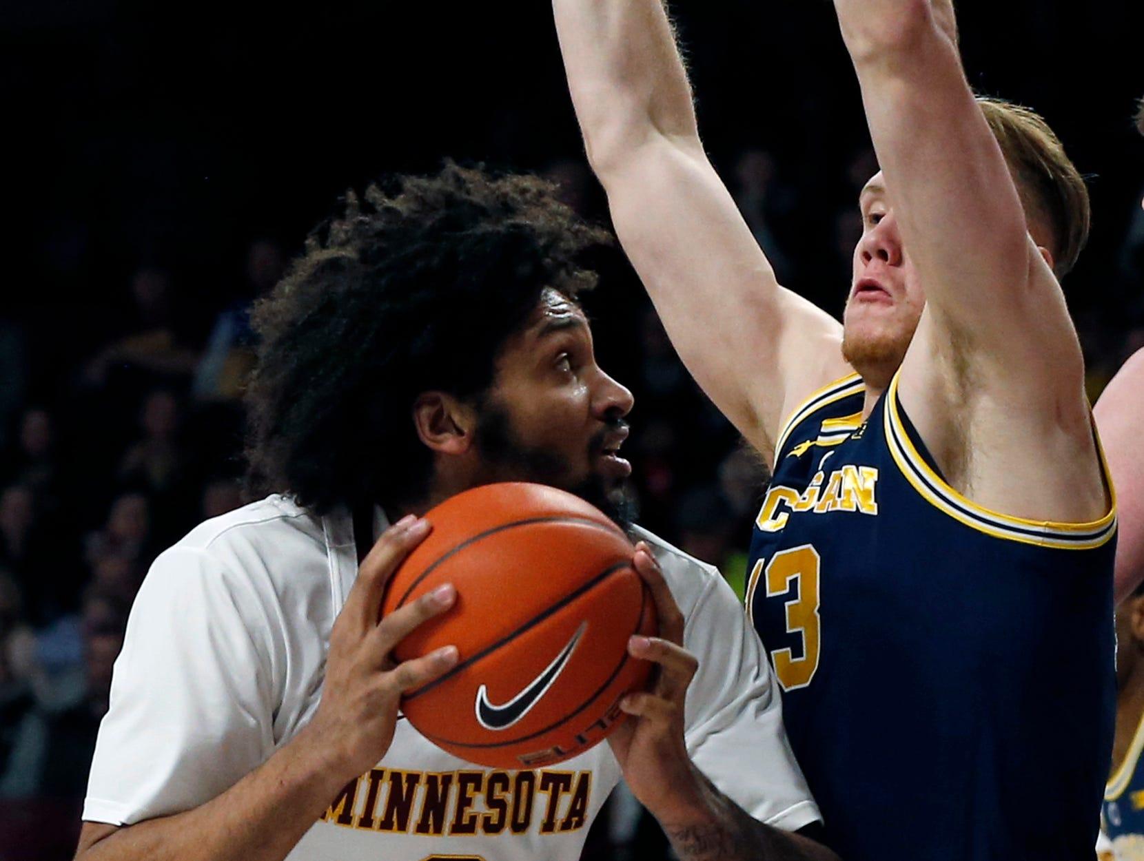 Minnesota's Jordan Murphy, left, tries to get around Michigan's Ignas Brazdeikis in the first half.