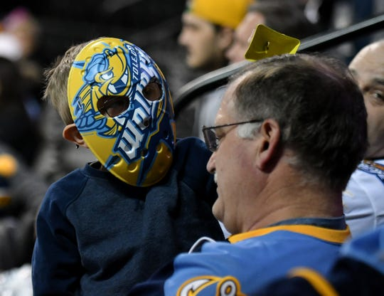 Attending his first Toledo Walleye game, Benjamin Havekost, 6, of Monroe rings a cowbell over the head of his grandfather, Brent Havekost, in the third period of game Jan. 31 against the Kalamazoo Wings at the Huntington Center in Toledo, Ohio.
