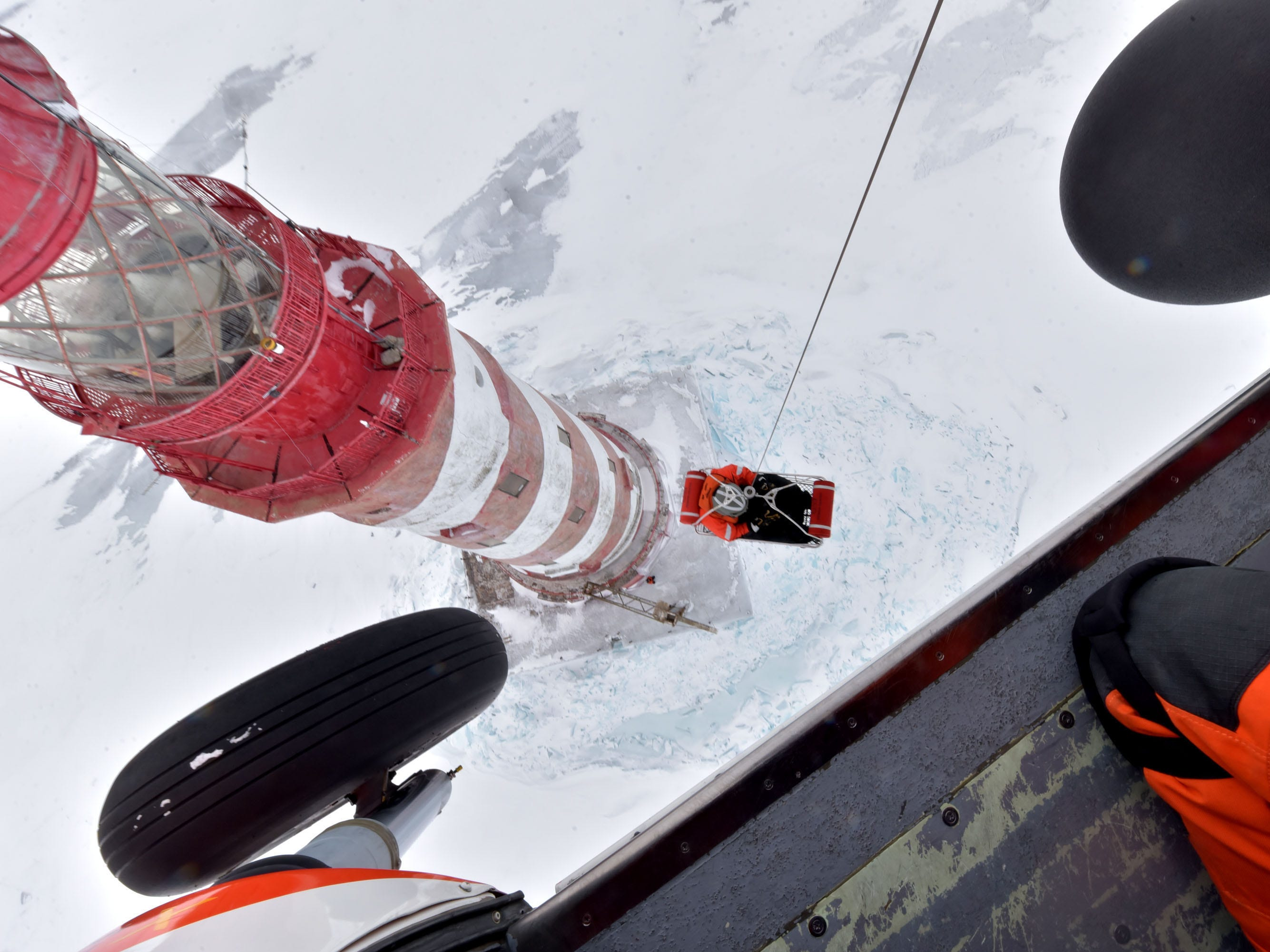 The U.S Coast Guard's Sean Roetnl is lifted from the deck of the White Shoal Lighthouse in upper Lake Michigan Thursday, Feb. 14, 2019 after performing maintenance and repair work.