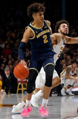 Michigan's Jordan Poole, who have five 3-pointers, breaks free of Minnesota's Gabe Kalscheur as he drives in the second half.