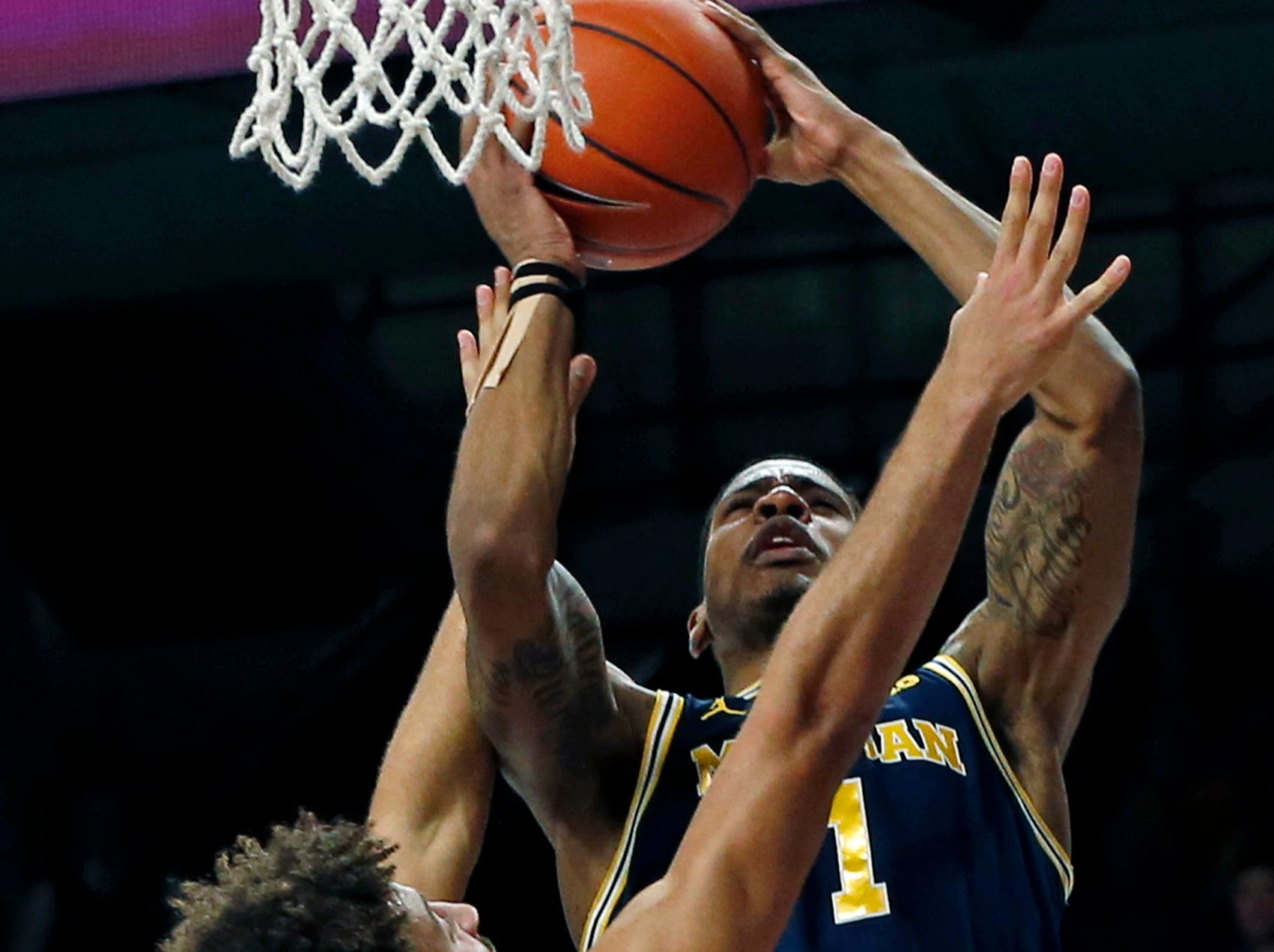 Michigan's Charles Matthews, right, shoots over Minnesota's Gabe Kalscheur in the second half.