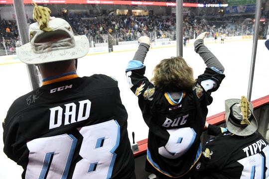 Katie McInerney, 9, of Sylvania, Ohio, cheers between her parents, Michael McInerney and Tammy McInerney, right, during the second intermission of a game between the Toledo Walleye and Kalamazoo Wings on Jan. 31 at the Huntington Center in Toledo, Ohio.  McInerney and his wife, Tammy, are wearing hats that Michael customized with walleye pinned to the tops and also featuring many player signatures. The family attends about 15 games a season.