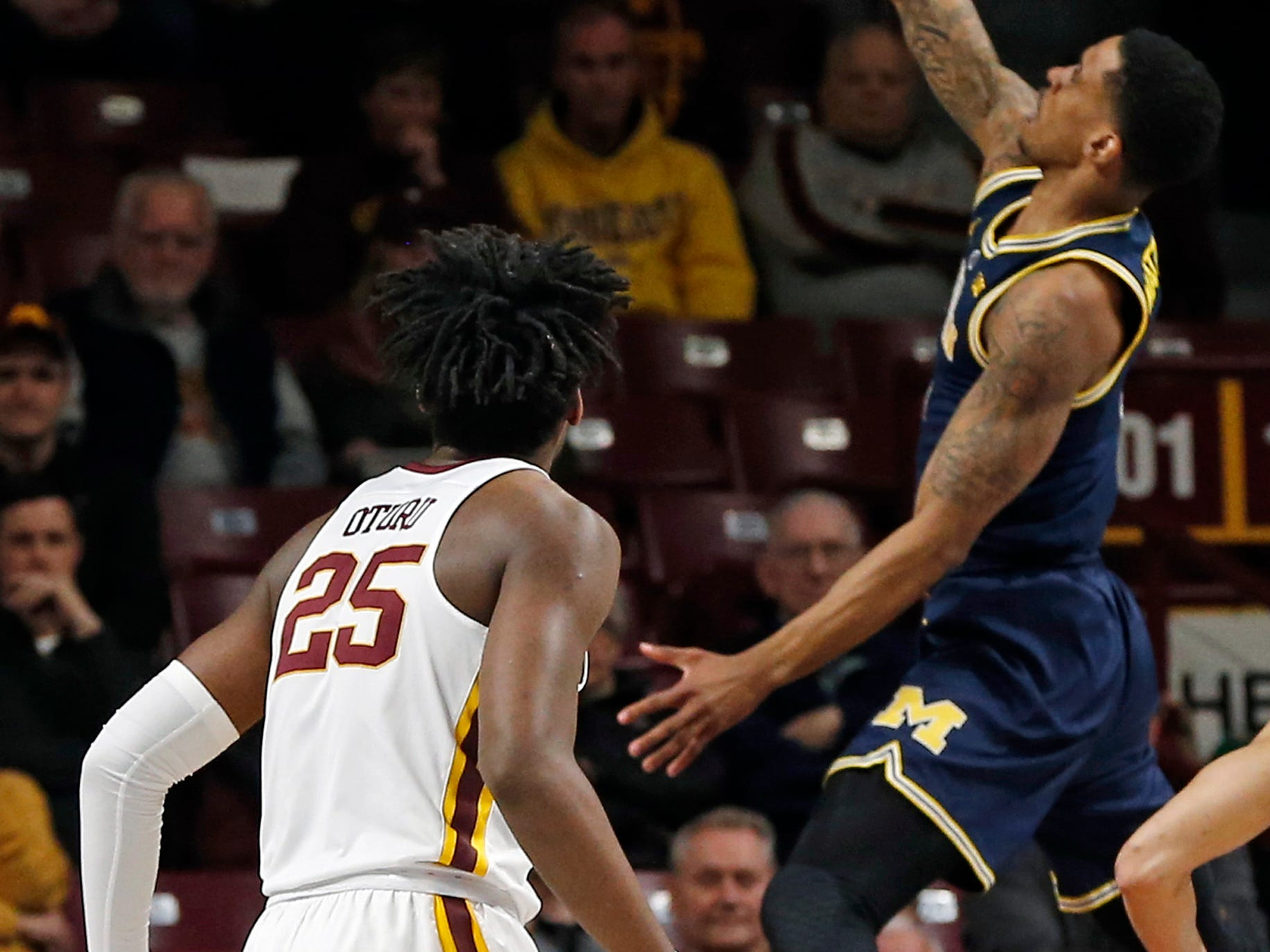 Michigan's Charles Matthews, right, lays up a shot as Minnesota's Daniel Oturu watches in the first half of an NCAA college basketball game Thursday, Feb. 21, 2019, in Minneapolis.