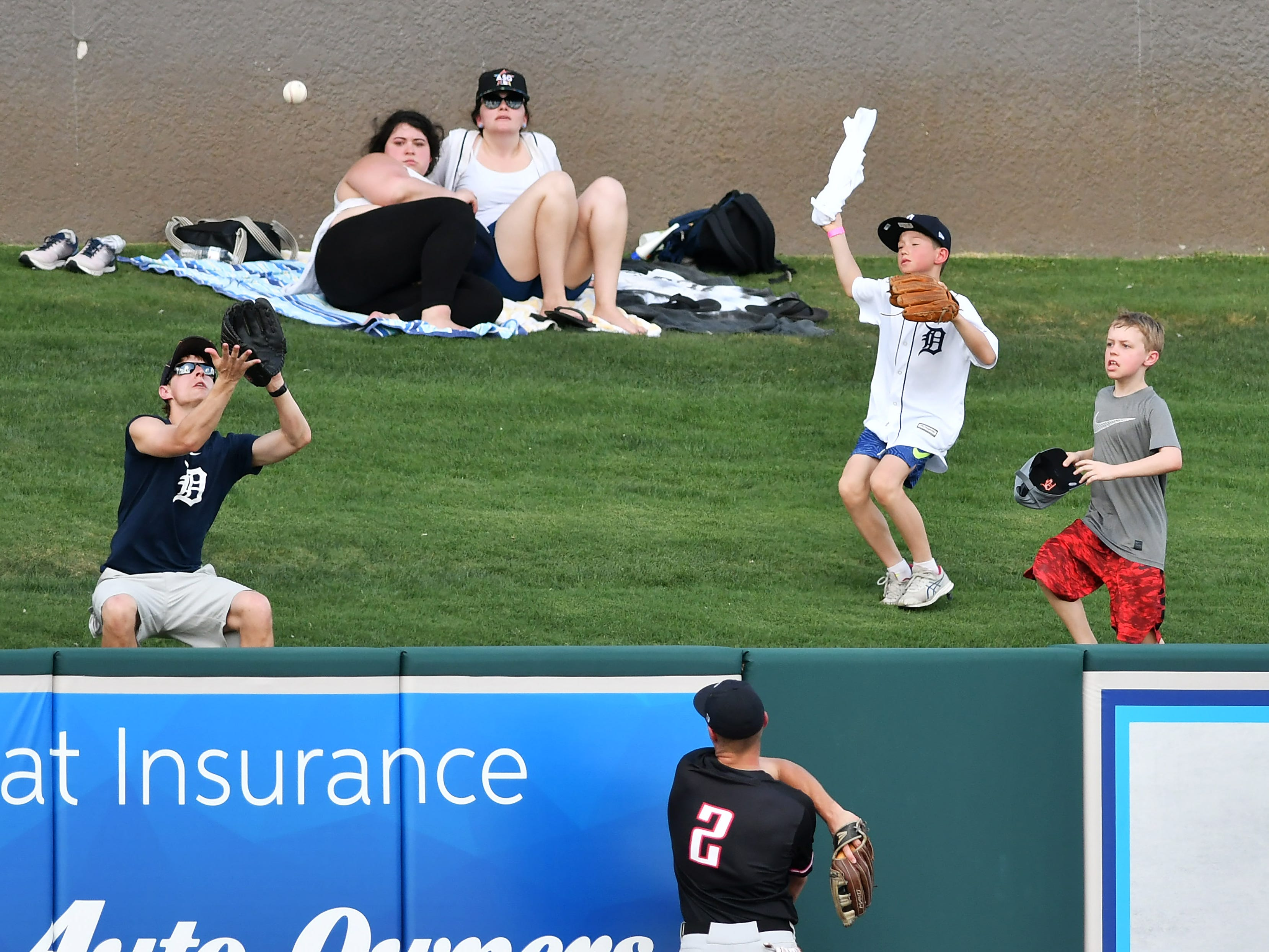 A fan is poised to catch the home run ball off the bat of Tigers' Jake Rogers in the third inning.