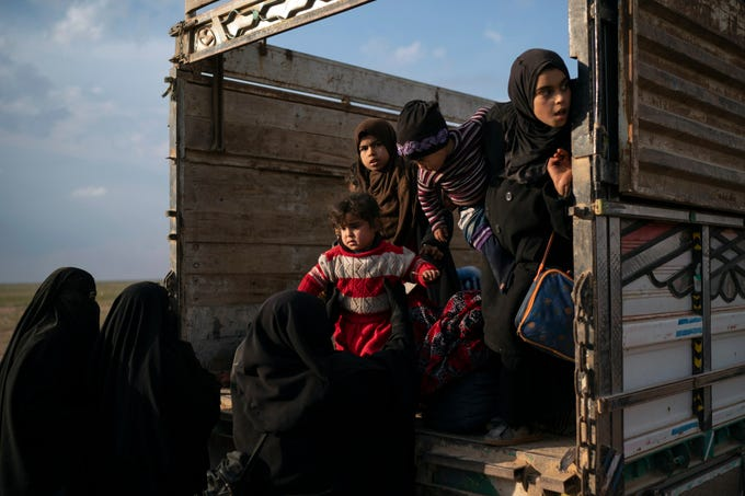Women and children exit the back of a truck, part of a convoy evacuating hundreds out of the last territory held by Islamic State militants in Baghouz, eastern Syria, Friday, Feb. 22, 2019.