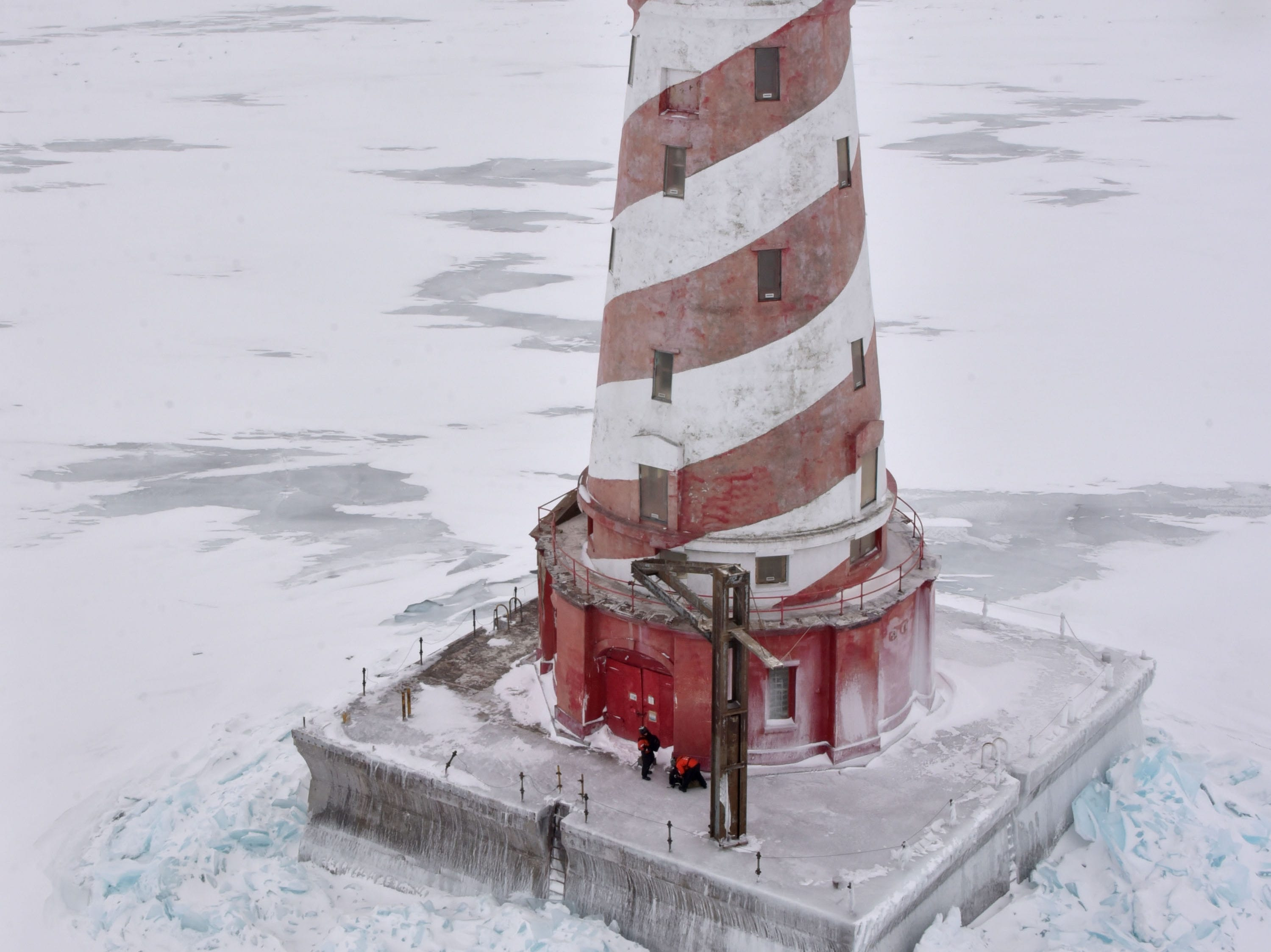 Two U.S. Coast Guard maintenance specialists wait on the deck of the White Shoal Lighthouse in upper Lake Michigan Thursday, Feb. 14, 2019 after performing maintenance on the high-powered light, which is 125-feet high. Several times a month an air crew from Air Station Traverse City places men on lighthouses as part of the Aids to Navigation project. All lights are automated and need to be kept operating all year.