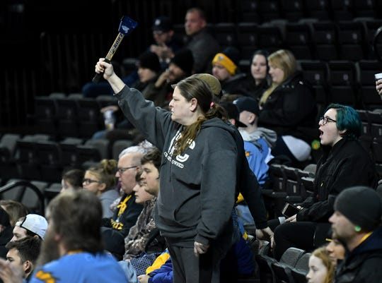 Wendy Laubenthal of Perrysburg, Ohio, makes noise with her cowbell in the first period of game Jan. 31 at the Huntington Center in Toledo, Ohio.  Laubenthal was at the game with Jon Burkett, to her right, and seated behind her is her daughter, Emily Laubenthal, 15, far right.