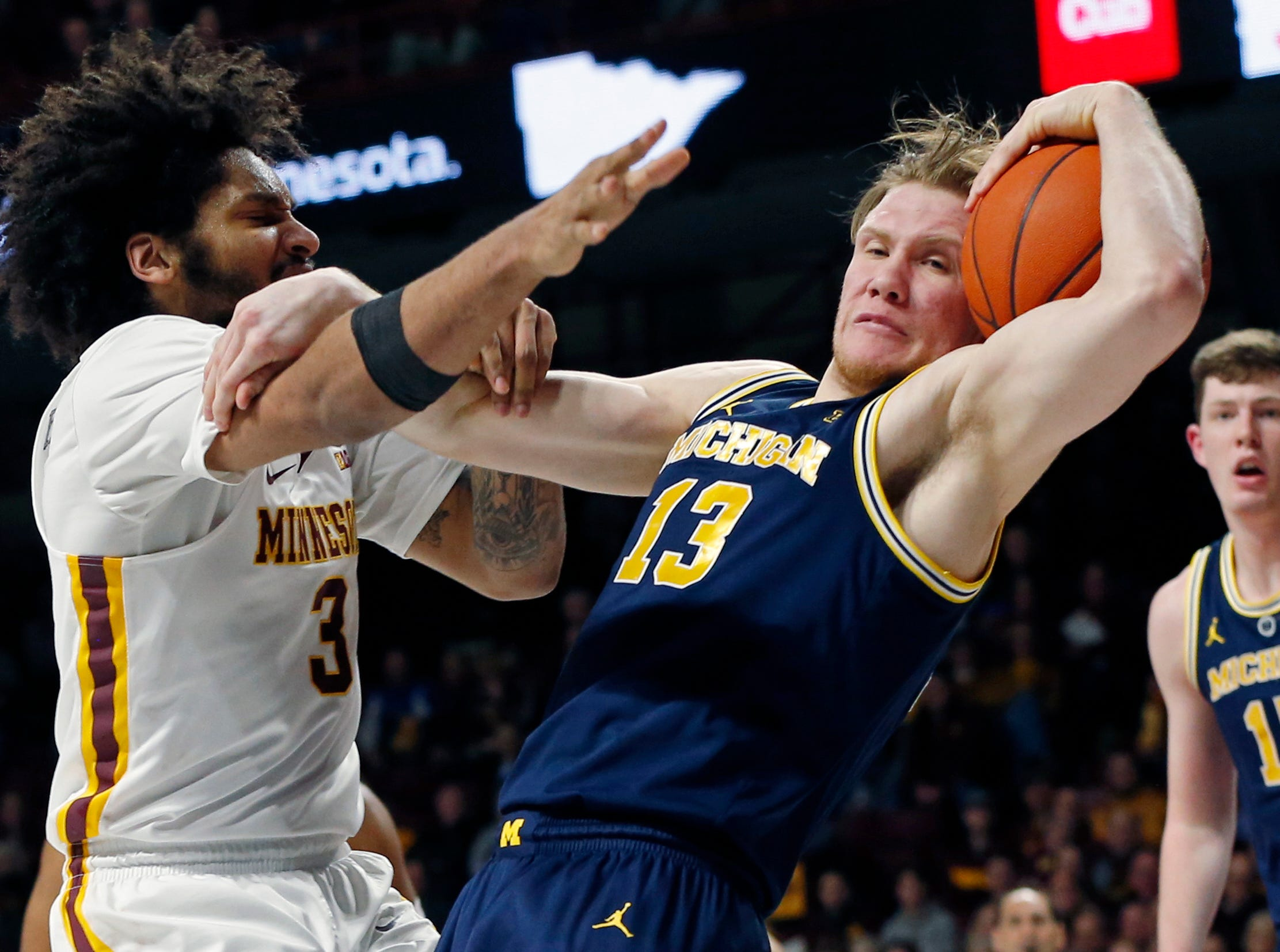Michigan's Ignas Brazdeikis, front right, tries to keep Minnesota's Jordan Murphy away from the ball in the first half.