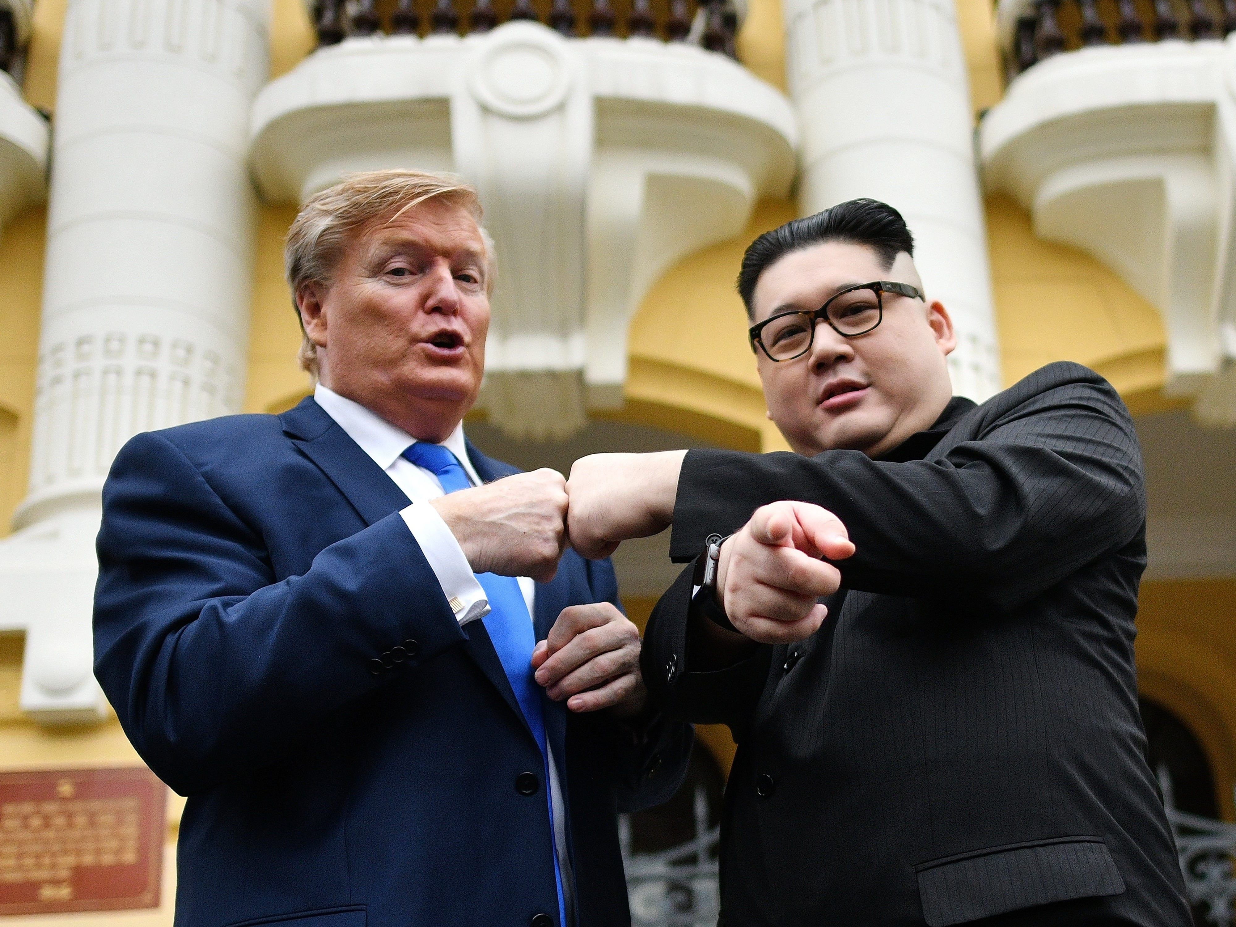 U.S. President Donald Trump impersonator Russel White and North Korean leader Kim Jong Un impersonator Howard X pose for photographs outside the Opera House in Hanoi on Feb. 22, 2019.