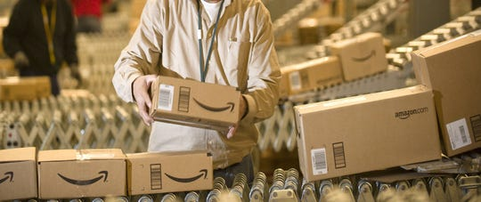 In this Monday, Dec., 1, 2008, file photo, an Amazon.com employee works at a  conveyor belt at the Fernley, Nev., warehouse. A former Amazon employee in Kentucky with the inflammatory bowel condition known as Crohn's disease has sued the company over his dismissal for what he says was a need for more bathroom breaks.