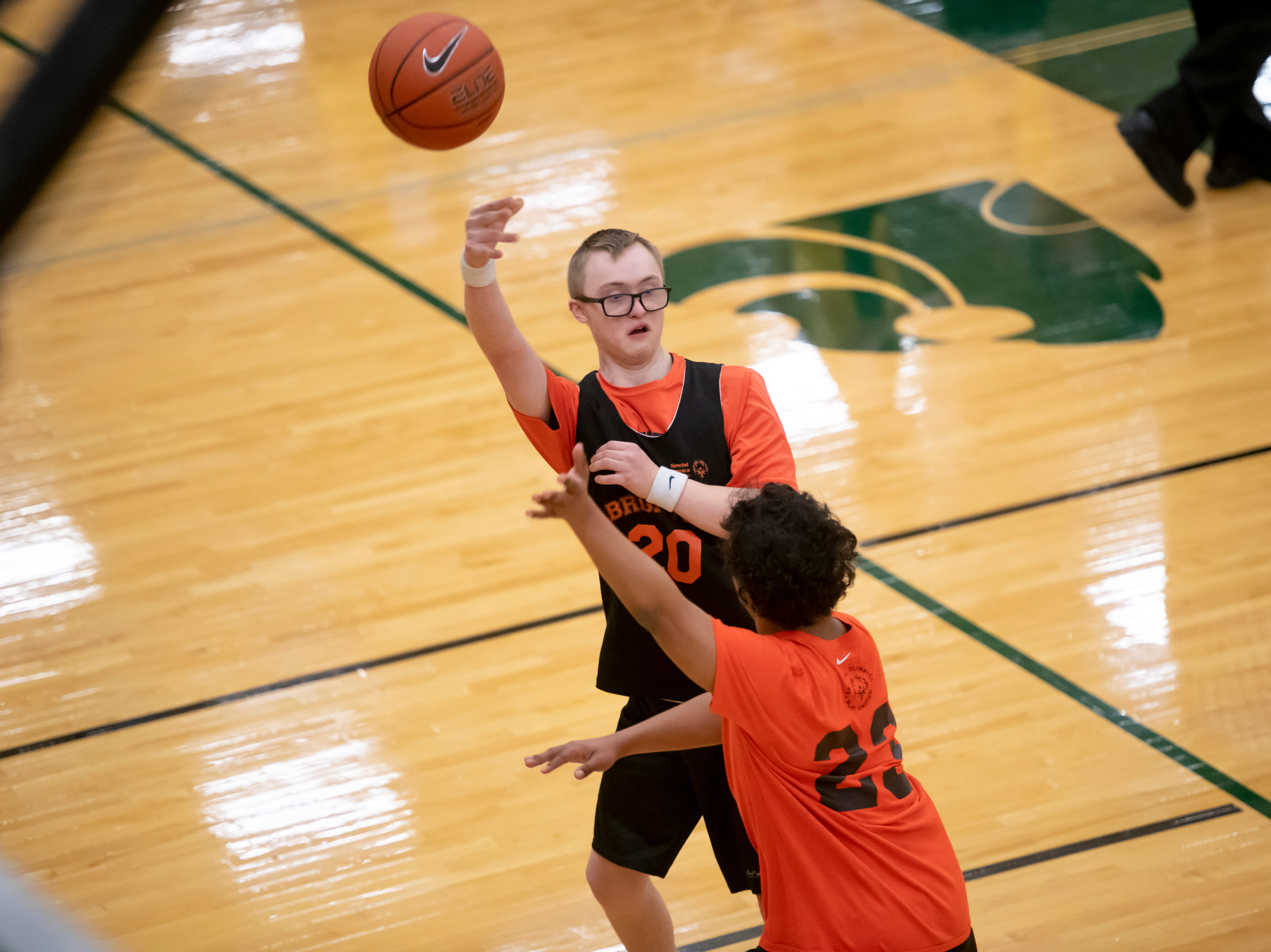 Brighton's Noah Johnson passes the ball around Northville Unified's Wolfgang Mueller during the Kensington Lakes Athletic Association Unified basketball tournament at Novi high school.