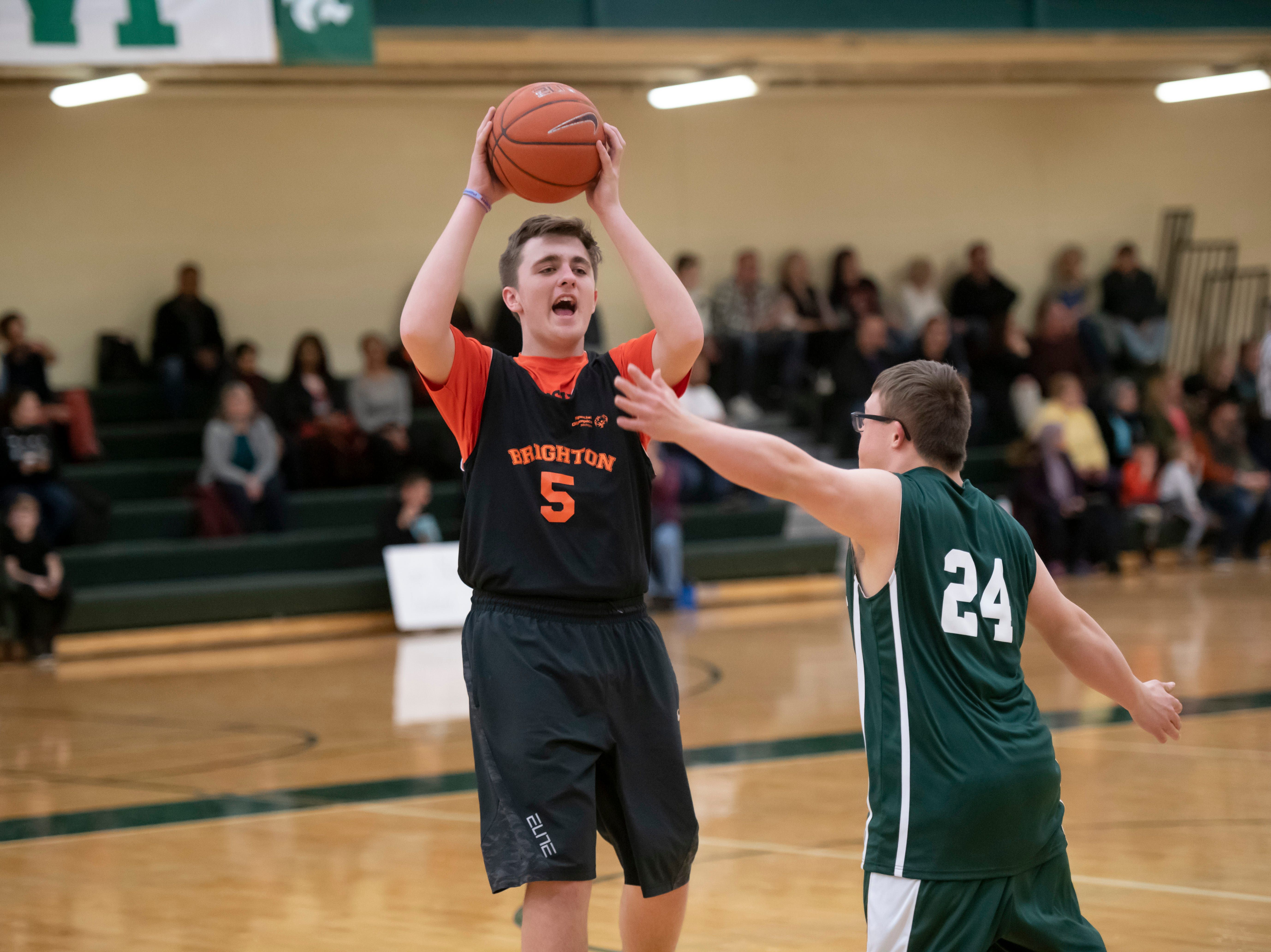 Brighton's Evan Potter looks for an open man while being defended by Novi's Robby Heil.