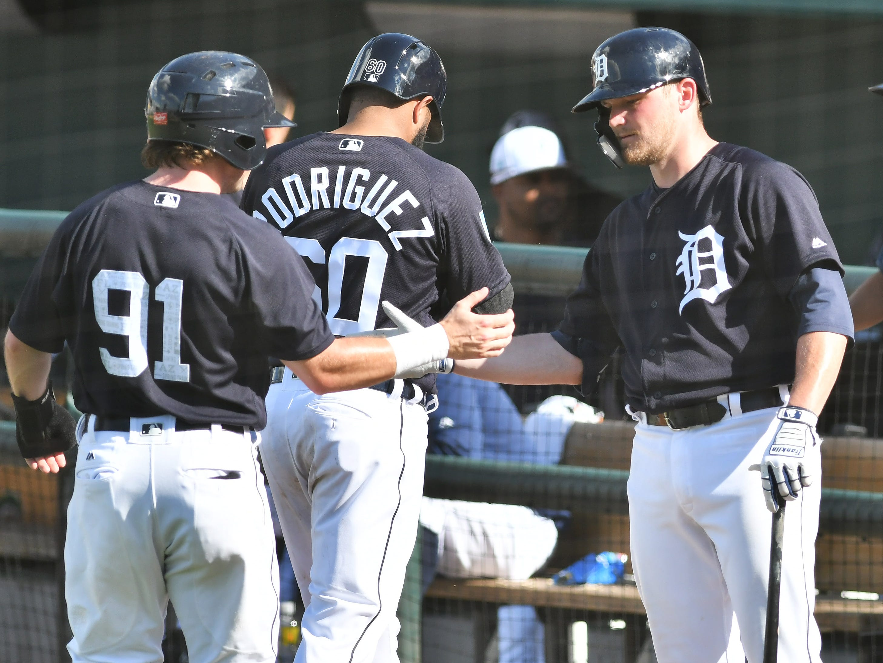 Tigers minor leaguer Kody Eaves congratulates Troy Montgomery (91) and Ronny Rodriguez after they score on a triple by Brady Policelli in the eighth inning.