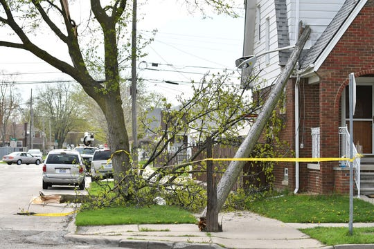 A large limb from a tree came down on power lines and caused a street light pole to snap and hit this home on Kendal Street after high winds cause damage in Dearborn, Mich. on May 4, 2018.