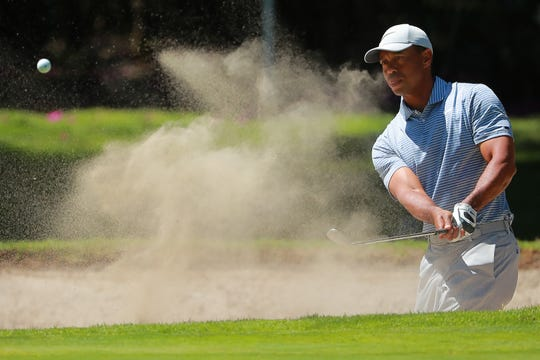 Tiger Woods hits out of a bunker during Thursday's first round.