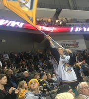 Season-ticket holder Michael Scott of Perrysburg, Ohio, waves the Walleye flag after a late goal cemented a 5-3 victory against Kalamazoo on Feb. 17 at the Huntington Center in Toledo, Ohio.