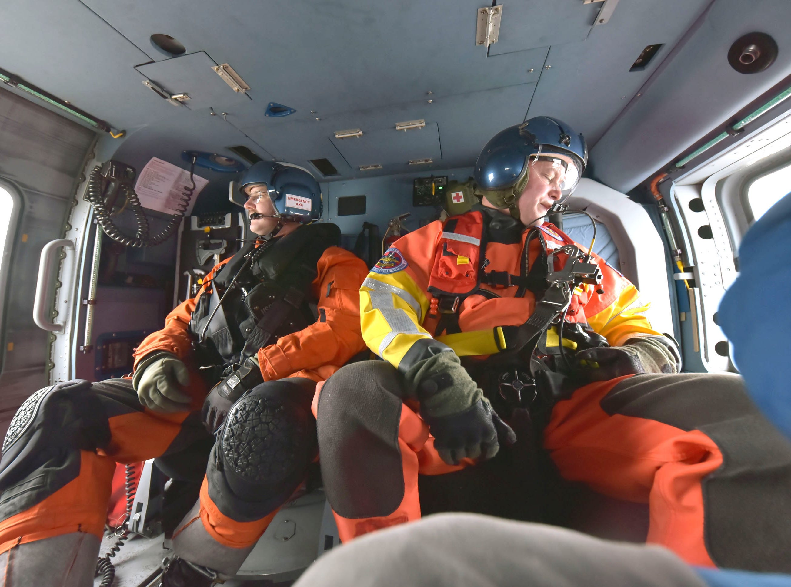 The U.S. Coast Guard's John Axelson, left, and Brad Fitspatrick settle into a flight aboard a MH-60T Jayhawk helicopter Thursday, Feb. 14, 2019 at Air Station Traverse City. The mission had the crew take aboard two Coast Guardsmen in St. Ignace and fly them to the White Shoal Lighthouse in upper Lake Michigan to perform maintenance and repairs on the lighthouse's beacon.