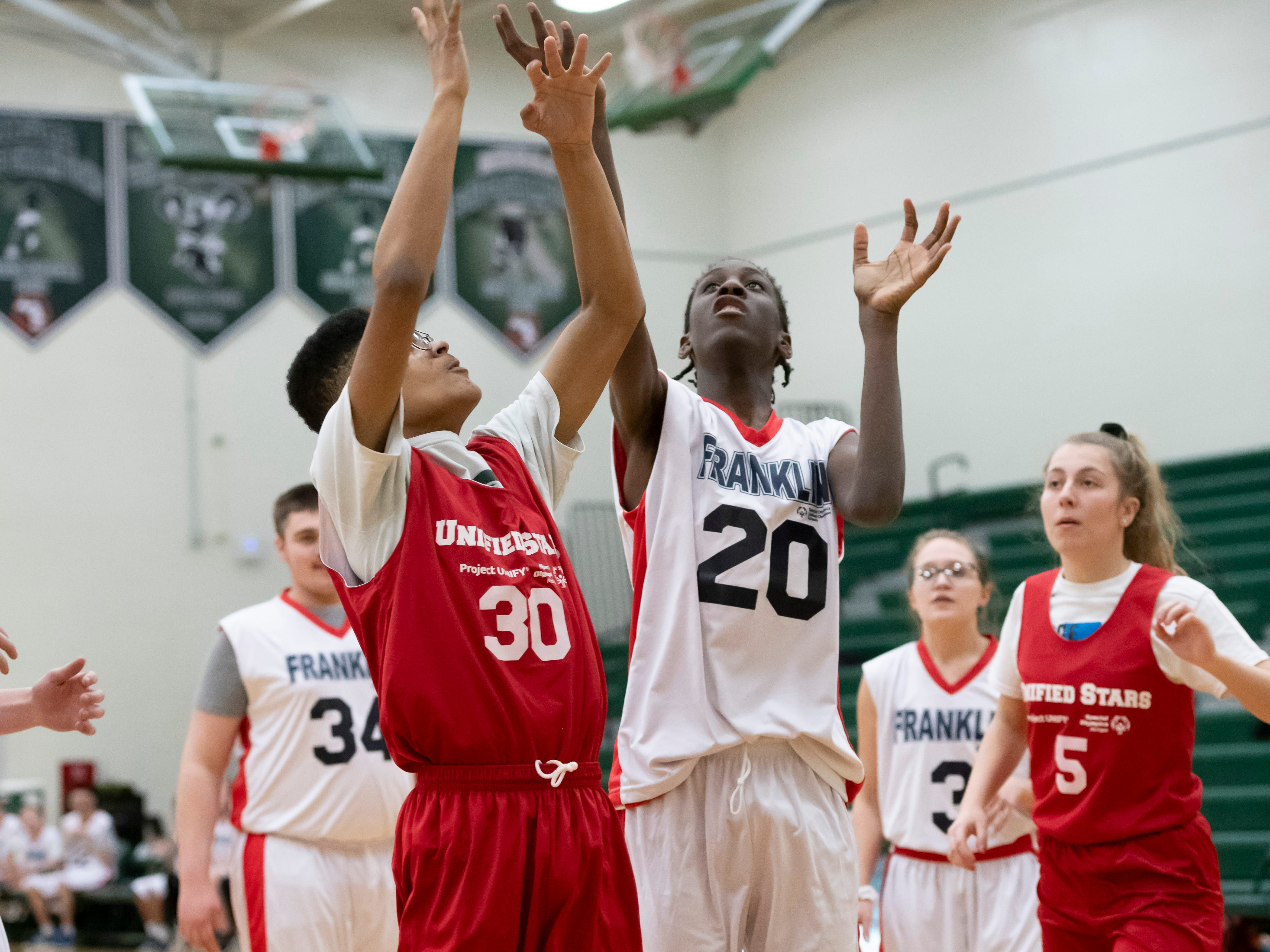 Plymouth Canton's Kamren Martin, left, and Franklin Unified's D.J. Rickett battle for the ball during the Kensington Lakes Athletic Association Unified basketball tournament at Novi high school.