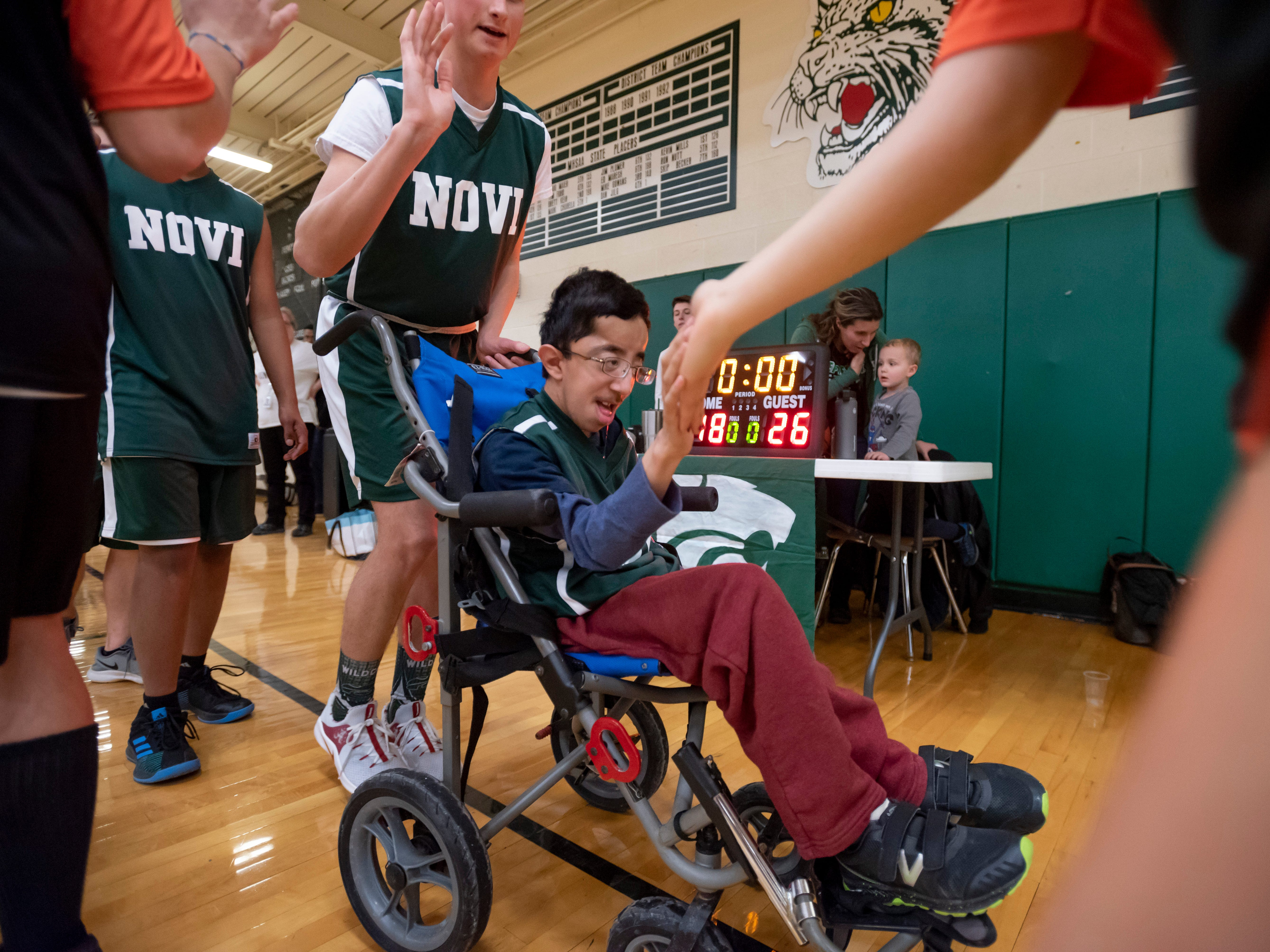 Members of the Novi team high five players from Brighton after a game during the Kensington Lakes Athletic Association Unified basketball tournament at Novi high school.
