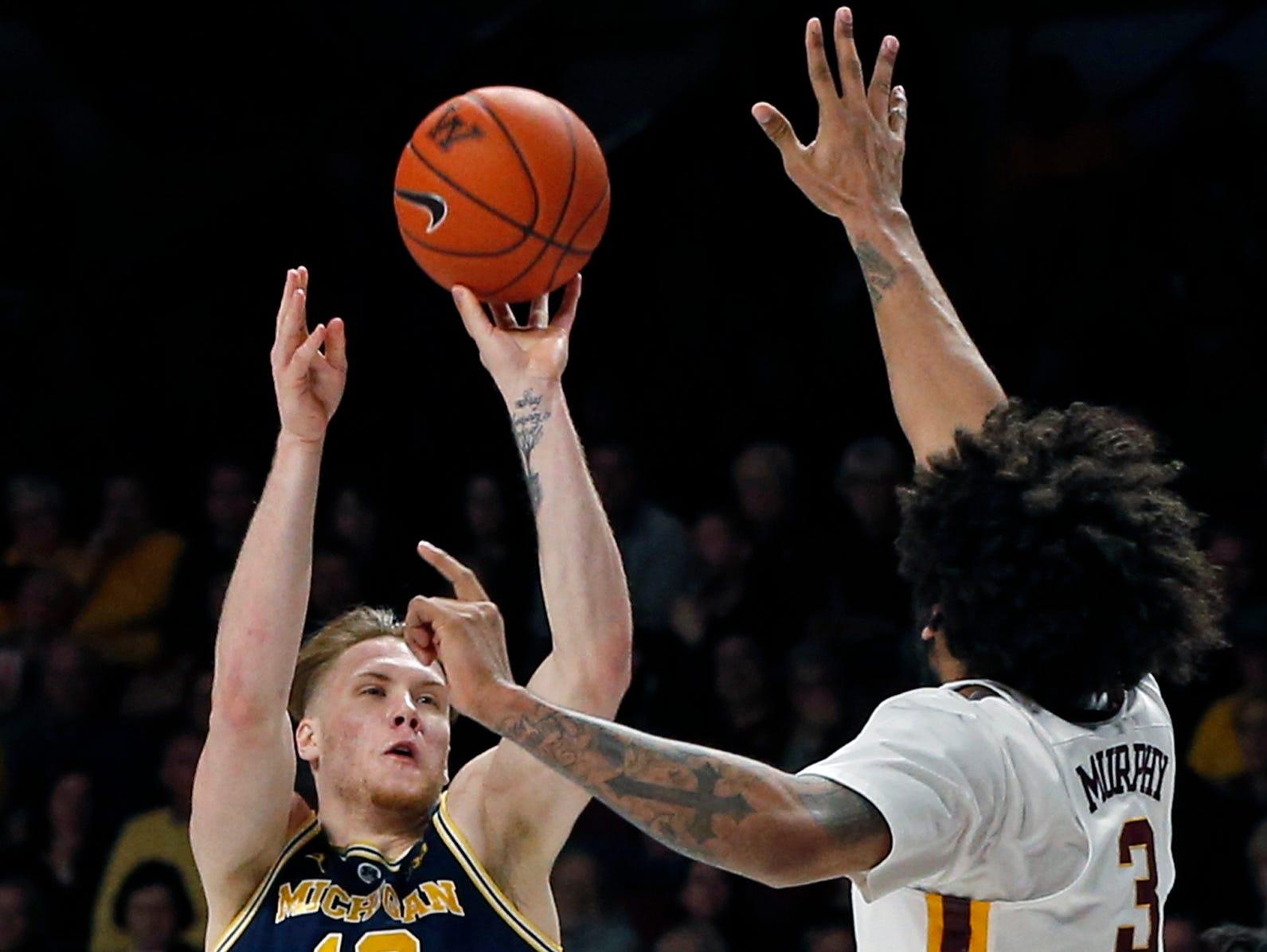 Michigan's Ignas Brazdeikis, left, shoots over Minnesota's Jordan Murphy in the second half of an NCAA college basketball game Thursday, Feb. 21, 2019, in Minneapolis. Michigan defeated Minnesota 69-60.