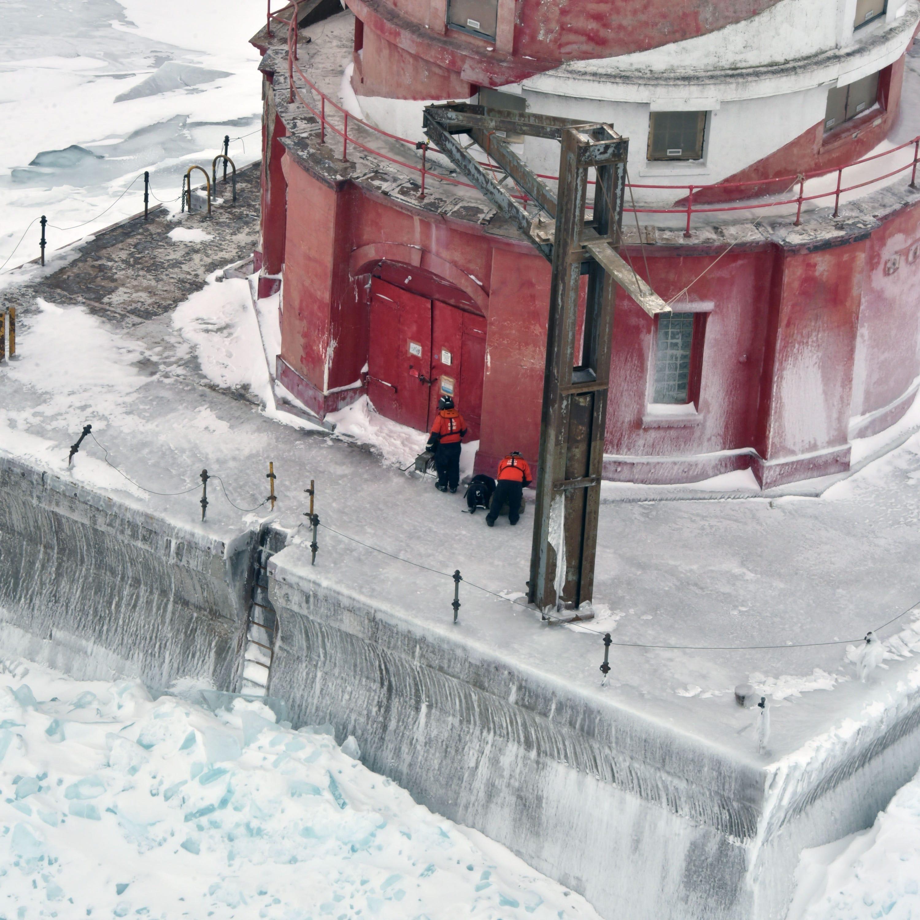 Two U.S. Coast Guard maintenance specialists wait...