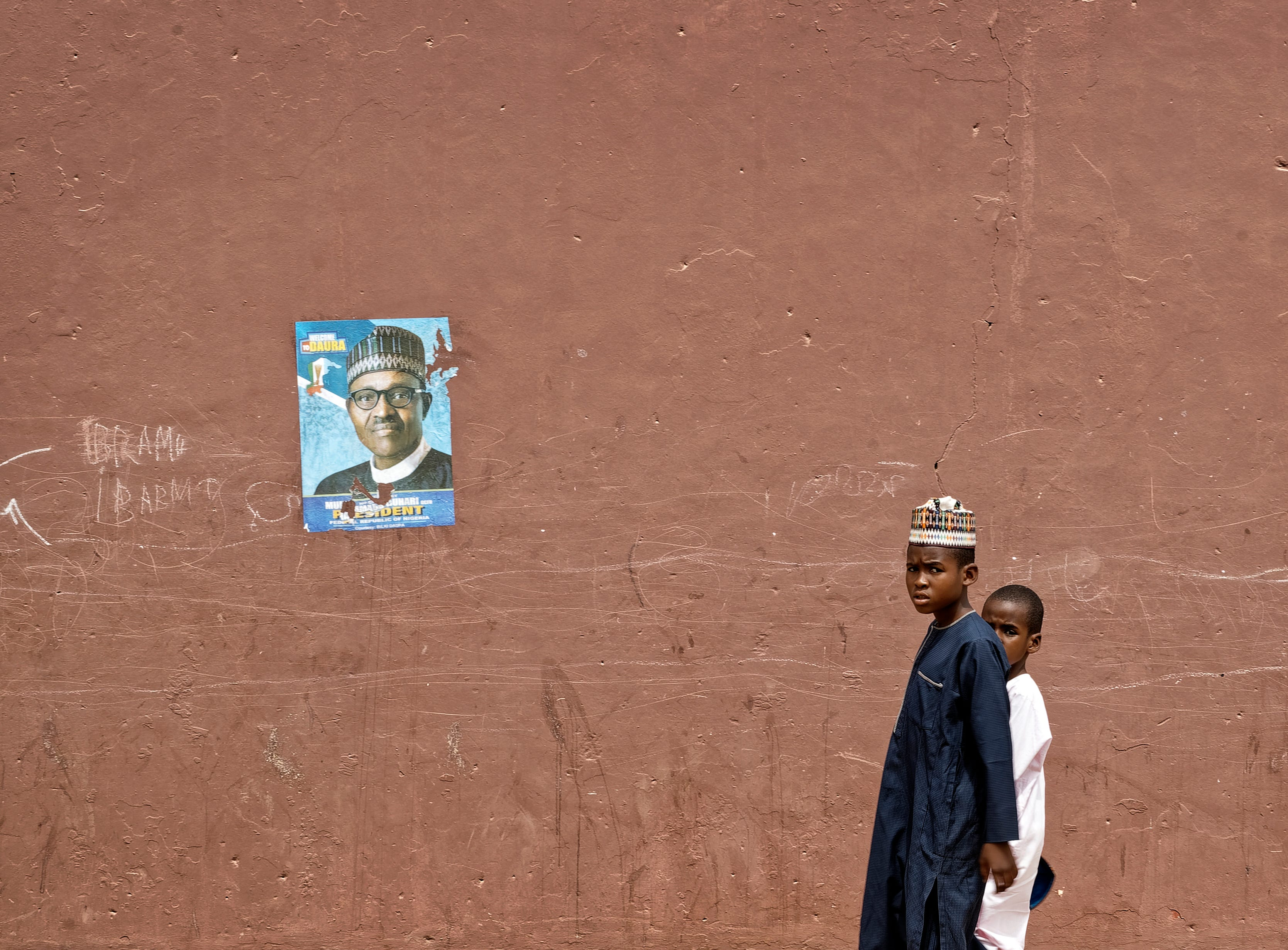 Two young boys walk home after traditional Muslim Friday prayers, past a campaign poster for President Muhammadu Buhari, outside the central mosque in his hometown of Daura, in northern Nigeria Friday, Feb. 22, 2019. Nigerians are preparing to go to the polls for a presidential election Saturday, one week after a surprise delay for Africa's largest democracy.