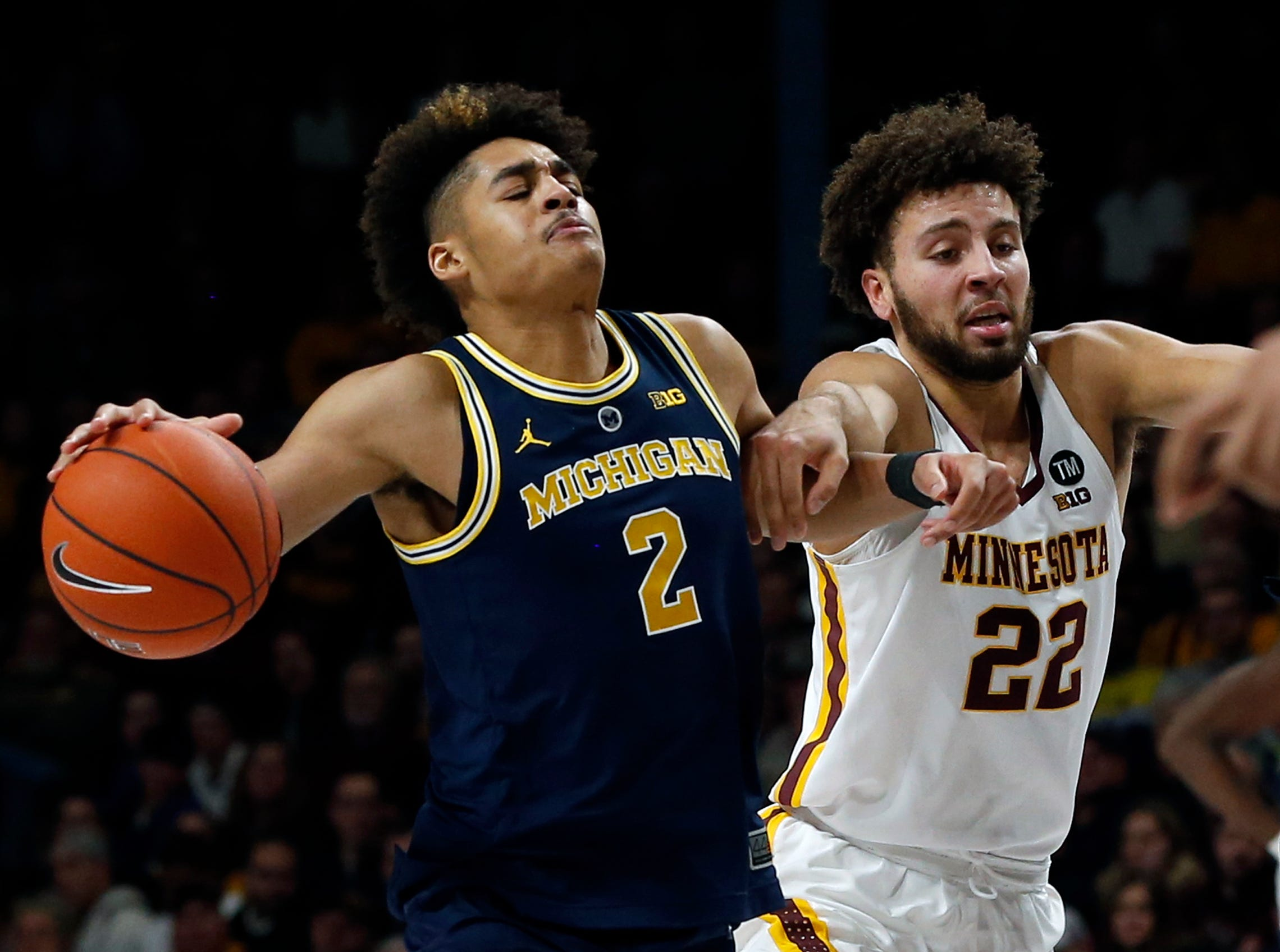 Michigan's Jordan Poole, left, drives as Minnesota's Gabe Kalscheur defends in the second half.