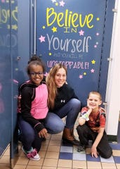 Local artist Kylene Kiah works with students to decorate bathroom stalls with inspirational quotes as part of Elmira's community schools initiative.