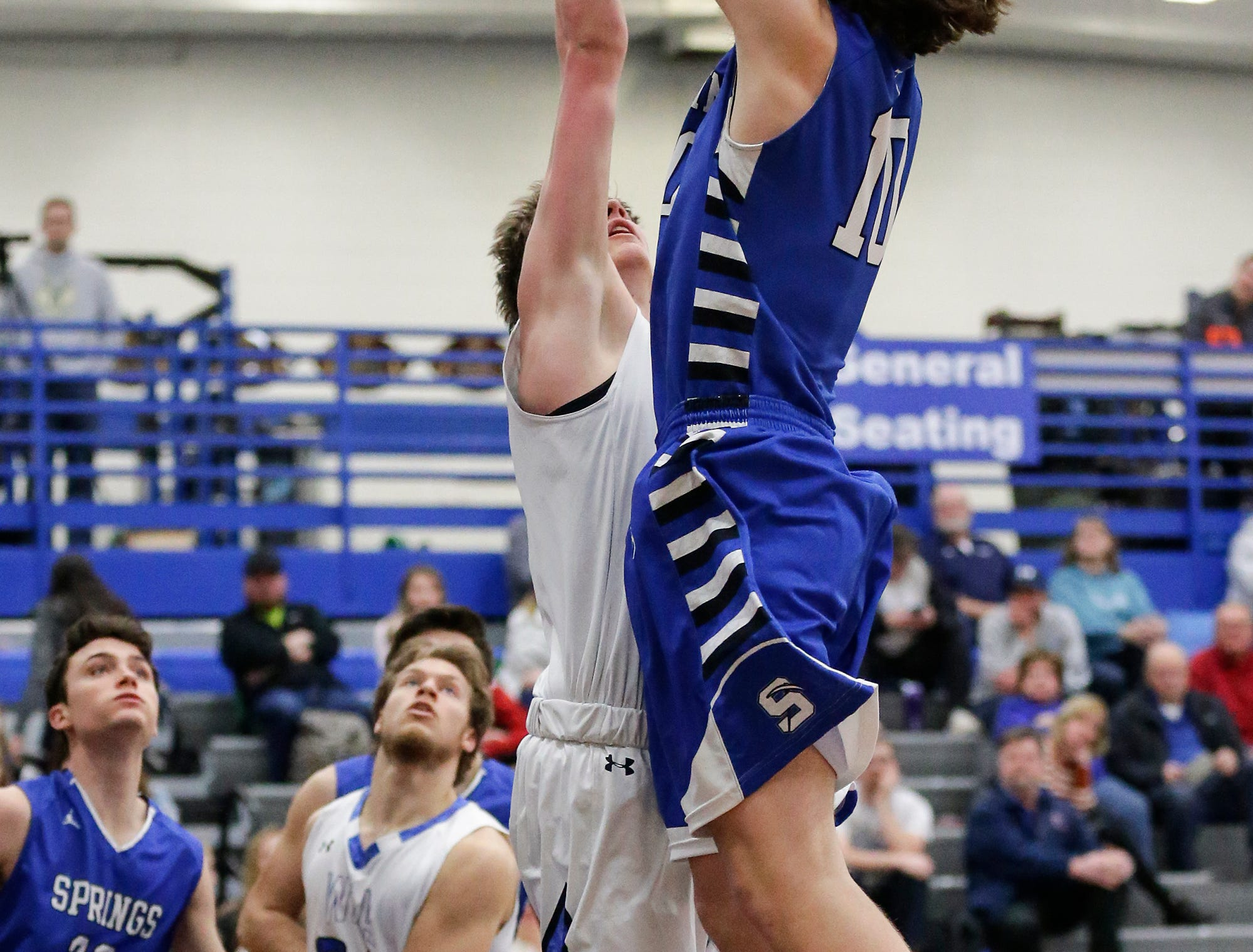 St Mary's Springs Academy boys basketball's Cade Christensen (10) makes this basket over  Winnebago Lutheran Academy's Gabe Pruss  during their game Thursday, February 21, 2019 in Fond du Lac, Wisconsin. Winnebago Lutheran Academy won the game 95-86. Doug Raflik/USA TODAY NETWORK-Wisconsin