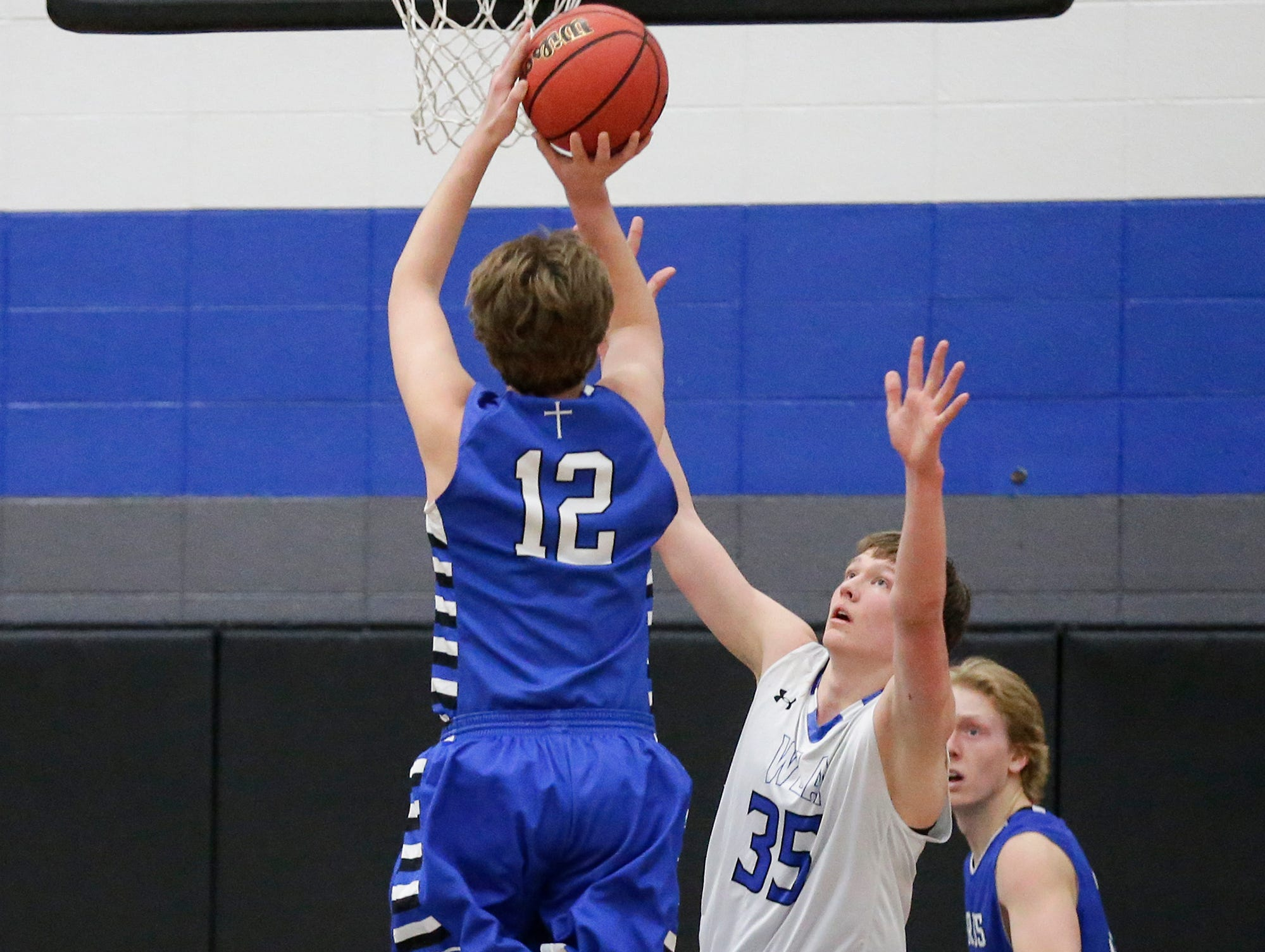 St Mary's Springs Academy boys basketball's Aiden Ottery (12) attempts a basket over Winnebago Lutheran Academy's Gabe Pruss (35) during their game Thursday, February 21, 2019 in Fond du Lac, Wisconsin. Winnebago Lutheran Academy won the game 95-86. Doug Raflik/USA TODAY NETWORK-Wisconsin