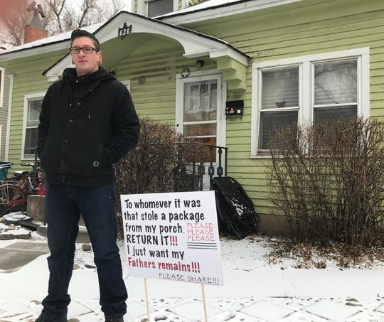 Austin Barker stands outside his duplex Friday with the sign he put out asking the person who stole his father's ashes sent in a package to return them.
