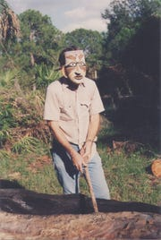 Dick Workman took replicating Calusa craftsmanship seriously ...  but not too seriously. Here' he works with a shell adze to hollow out a slash pine canoe wearing a mask he'd carved from gumbo limbo and decorated with paint made from natural pigments using strangler fix latex as the vehicle.