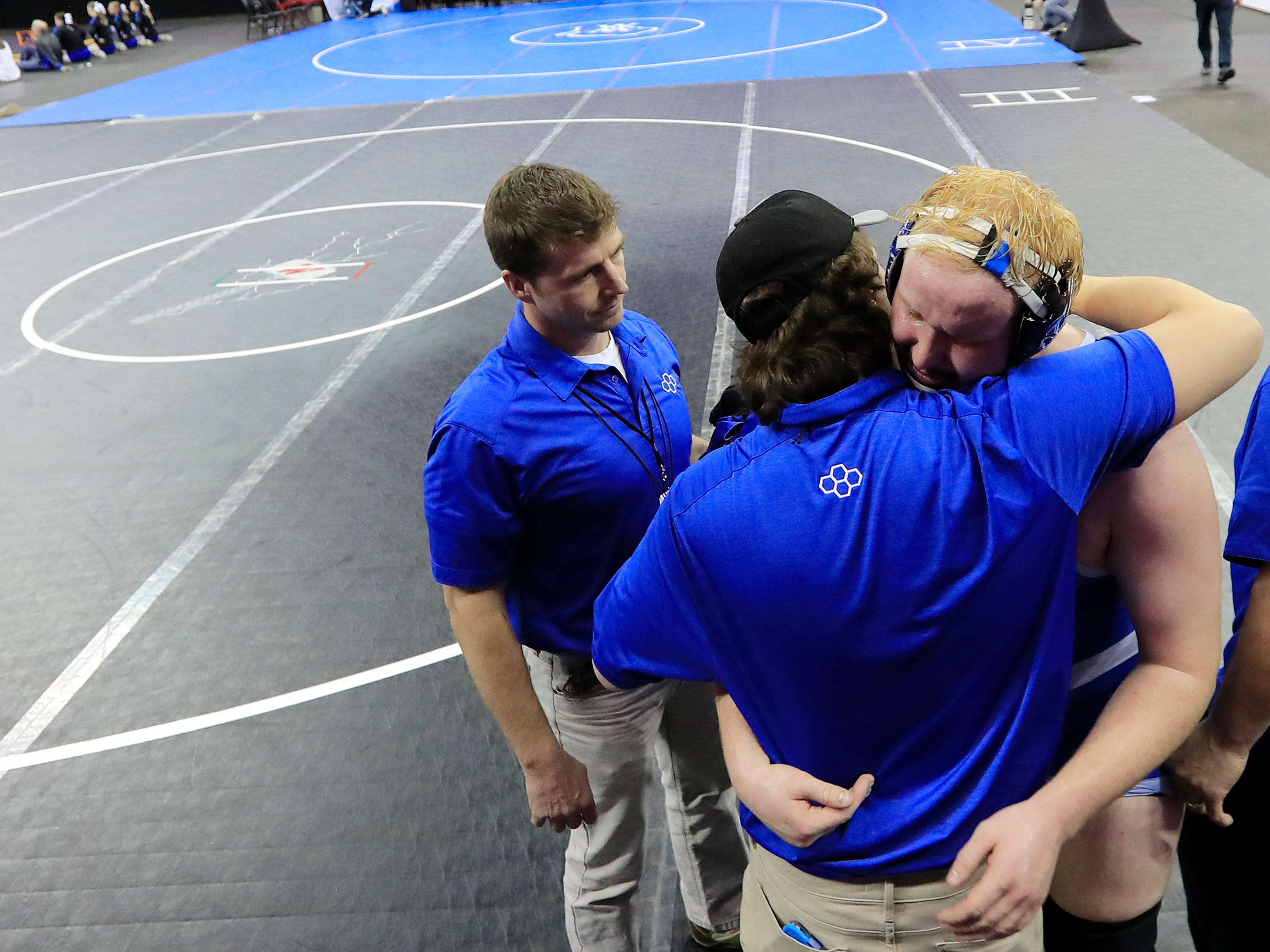 Wrightstown's Ethan Witcpalek hugs his coaches after losing in a Division 2 285-pound preliminary match at the WIAA state individual wrestling tournament at the Kohl Center on Thursday, February 21, 2019 in Madison, Wis.