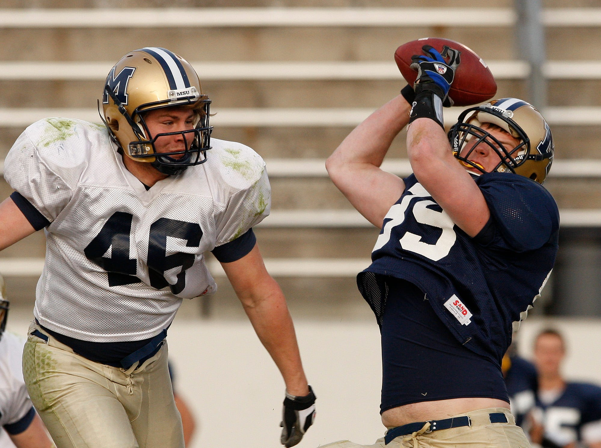 Tribune Photo/Larry BecknerBobcat tight end Steven Foster catches a third quarter pass as Ryan D'Agostino defends during the Triangle Classic Spring Game at Memorial Stadium Saturday night.