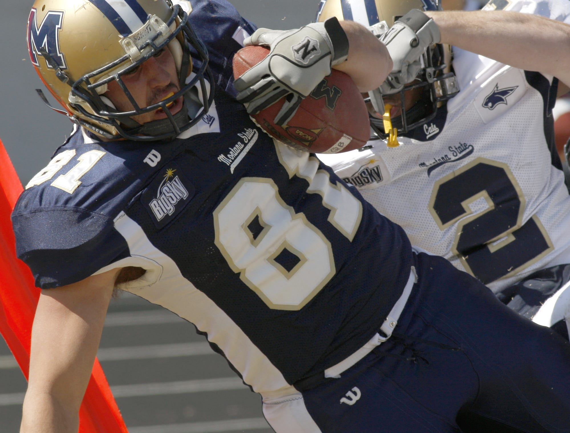 Kyle Begger (81) is tackled after making a catch by David Taylor (2) near the end zone during Montana State Universities Triangle Classic scrimmage Saturday at Memorial Stadium.