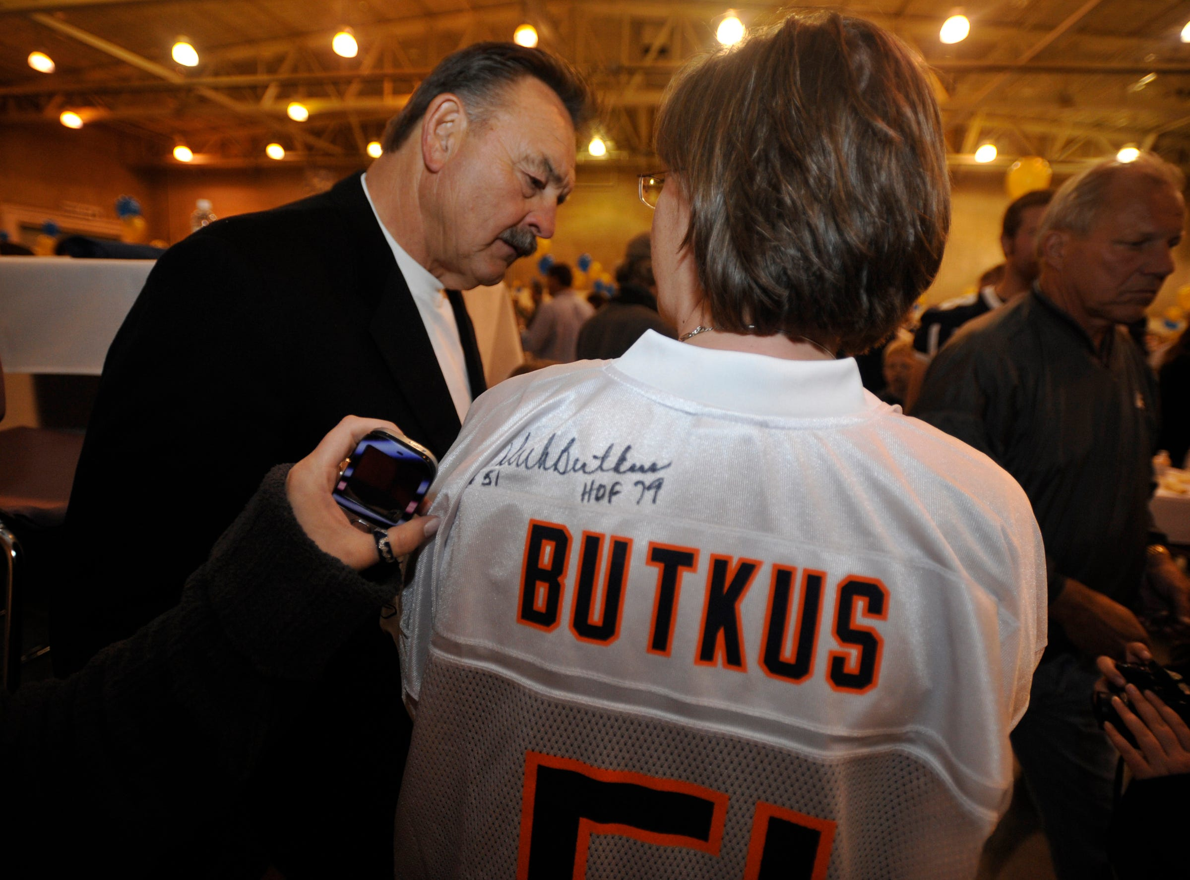 Marilyn Snezek of Helena, a longtime Chicago Bears and MSU Bobcats fan, talks with guest speaker, NFL Hall-of-Famer Dick Butkus before Friday night's Triangle Classic banquet in Exhibition Hall.