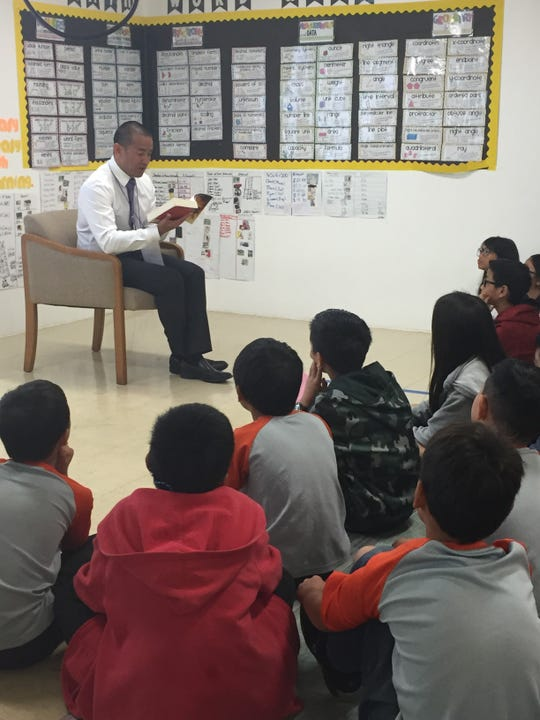 Attorney General Levin Camacho reads an excerpt from Roald Dahl's Book of Ghost Stories to a fifth-grade class at iLearn Academy Charter School during the schools' Read-a-Thon spirit week celebration.