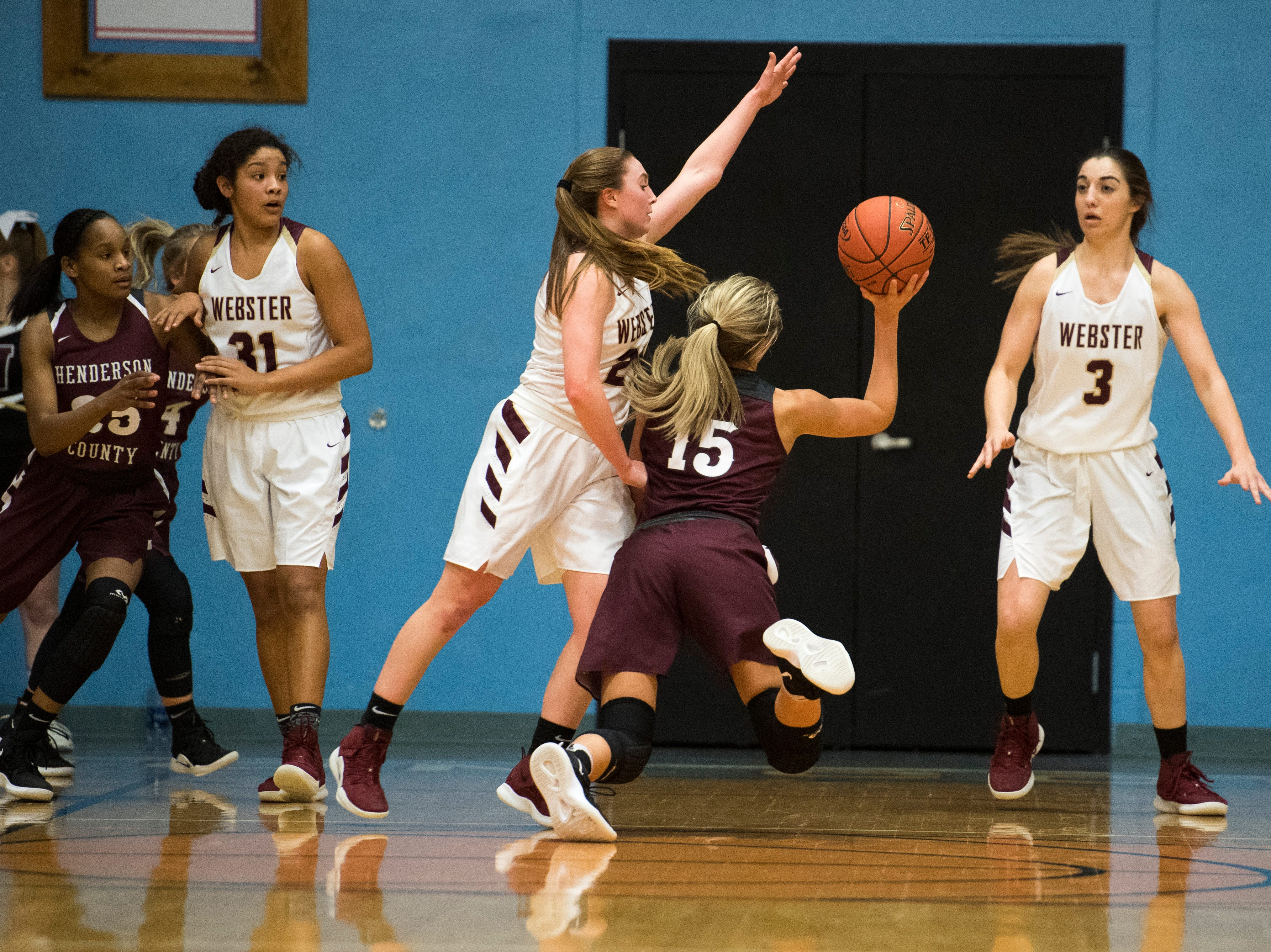 Henderson County's Alyssa Dickson (15) takes a shot while falling to the floor during the 2019 Sixth District championship game against the Webster County Lady Trojans at Union County High School Thursday, Feb. 21, 2019.