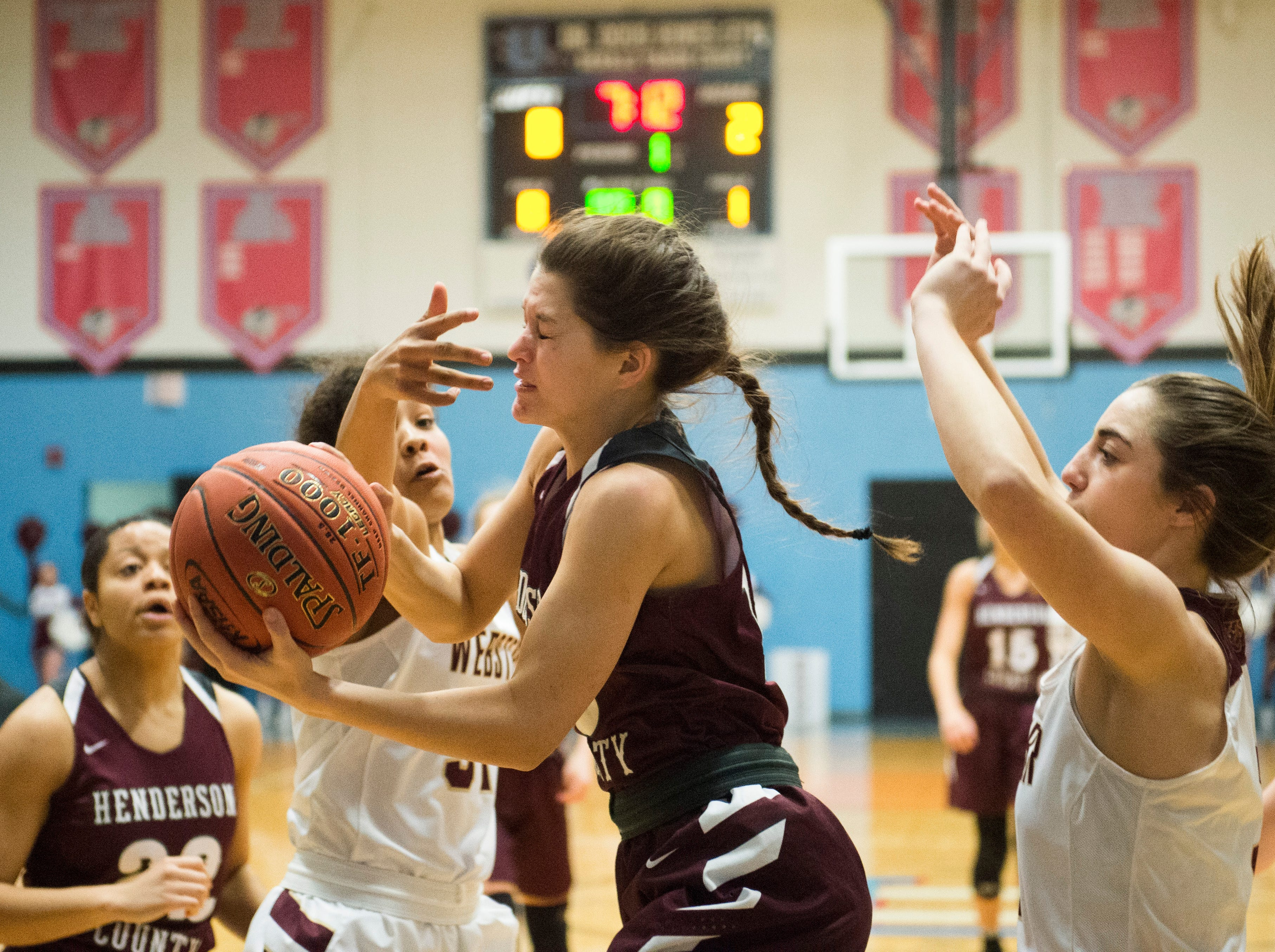 Henderson County's Katie Rideout (10) pulls down a rebound during the 2019 Sixth District championship game against the Webster County Lady Trojans at Union County High School Thursday, Feb. 21, 2019.