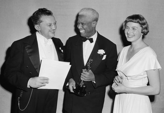 "Jean Hersholt, President of Academy of Motion Pictures Arts and Sciences, congratulates James Baskett, center, second African American  to win an Oscar, for his special award for his portrayal of Uncle Remus in the 1946 Disney feature film ""Song of the South"" on March 20, 1948 in Los Angeles, Calif.. Looking on is Ingrid Berman, who made presentation to Baskett. (AP Photo)"