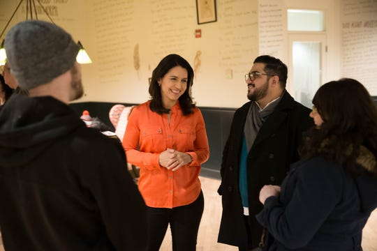 2020 Democratic presidential candidate Tulsi Gabbard, center, speaks with Armando Cardenas of Washingon, second from right, and other supporters in the lobby of the Graduate in Iowa City on Thursday, February 21, 2019.