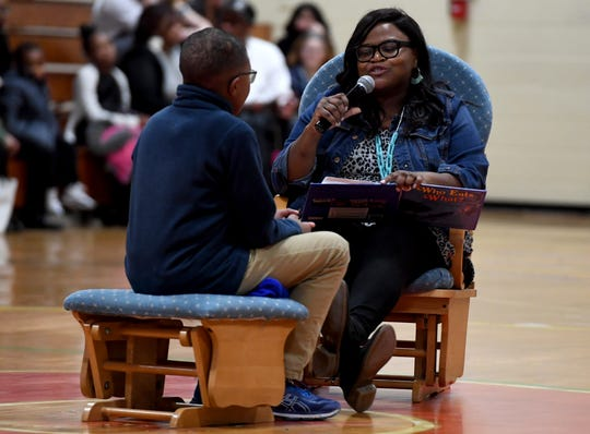 """East Elementary School teacher Tekia Denwiddie reads """"Mother to Son"""" by Langston Hughes to her son Dallas Weddle during the school's 2019 Black History Month program, Thursday, Feb. 21."""