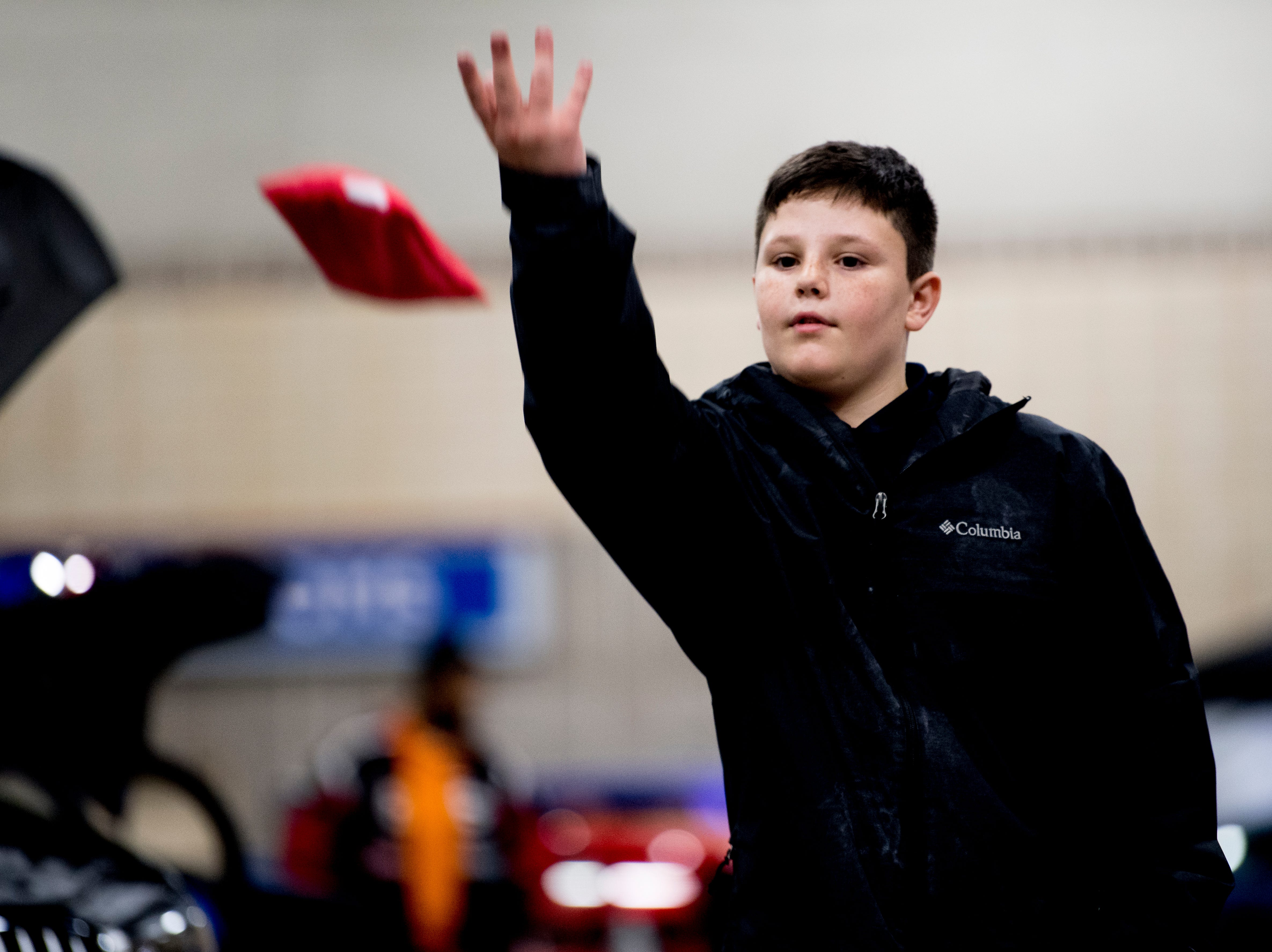 Isaac Evans plays corn hole with his sister at the Knox News Auto Show preview party in the Knoxville Convention Center in Knoxville, Tennessee on Thursday, February 21, 2019.