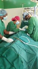 Surgeon Jovenel Cherenfant, MD, right, performed a thyroidectomy with a surgical technician and another American surgeon in Atibie, Ghana. The three volunteer their services through Anidaso Health of Chicago, Illinois.